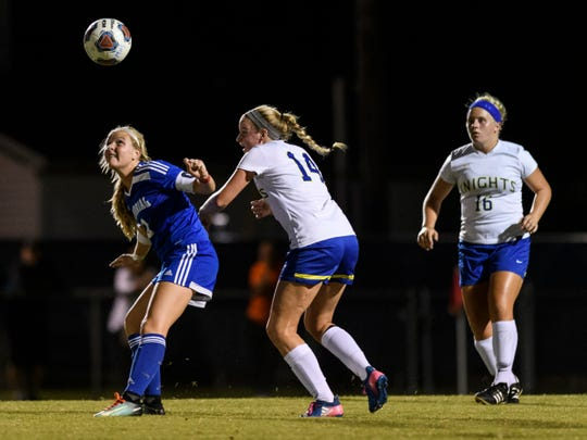 Memorial's Isabel Alexander (2) heads the ball away from Castle's Katie Steenberg (14) during the second half at Traylor Family Stadium in Evansville, Ind., Tuesday, Sept. 11, 2018.