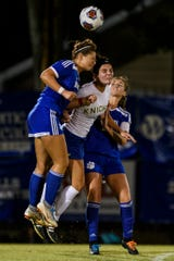 Castle's Avery McKinney (11) goes head-to-head with Memorial's Elle Unfried (19) and Memorial's Annah Hopkins (18) while fighting for possession of the ball at Traylor Family Stadium in Evansville, Ind., Tuesday, Sept. 11, 2018. The Knights remain undefeated after a 2-1 victory over the Tigers.