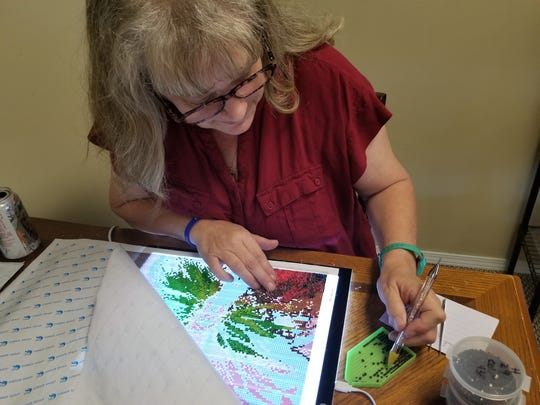 """Always willing to try new art projects, Batson is currently working on a """"diamond painting"""" in her moments of downtime at the studio."""
