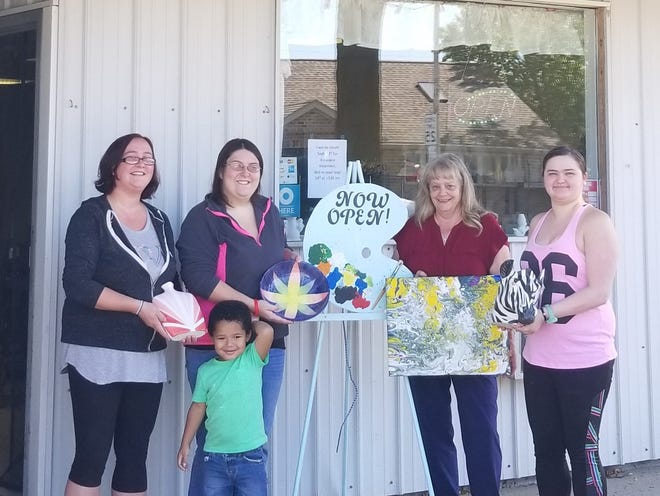Fired Visions Studio offers paint-your-own-pottery as well as commissioned pieces and paintings. Pictured starting left: Michelle Moon, Elliott Riley, Amber Riley, Paula Batson and Elizabeth Raven, show some of Batson's creations.