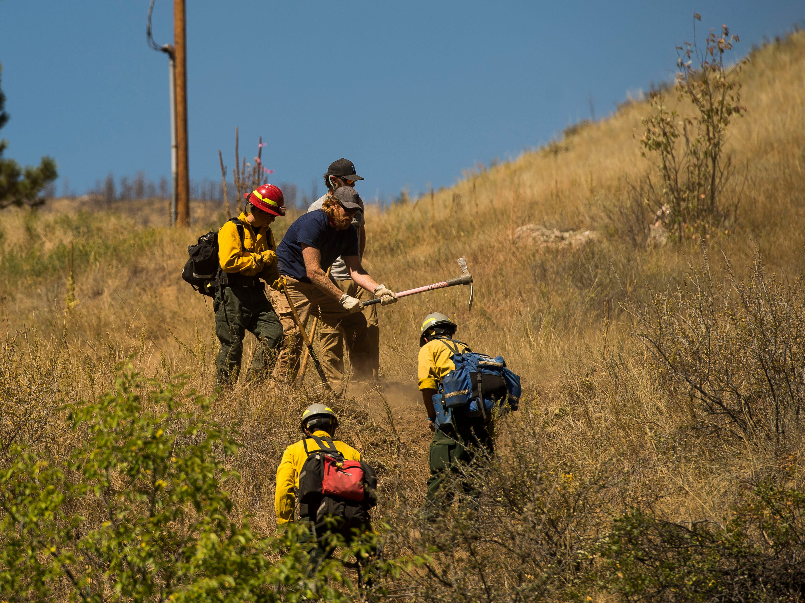 Backcountry firefighters dig a trench to act as a fireline up a hill from the Cache la Poudre River on Wednesday, Sept. 12, 2018, in the Poudre Canyon, near Seaman Reservoir in Larimer County, Colo.