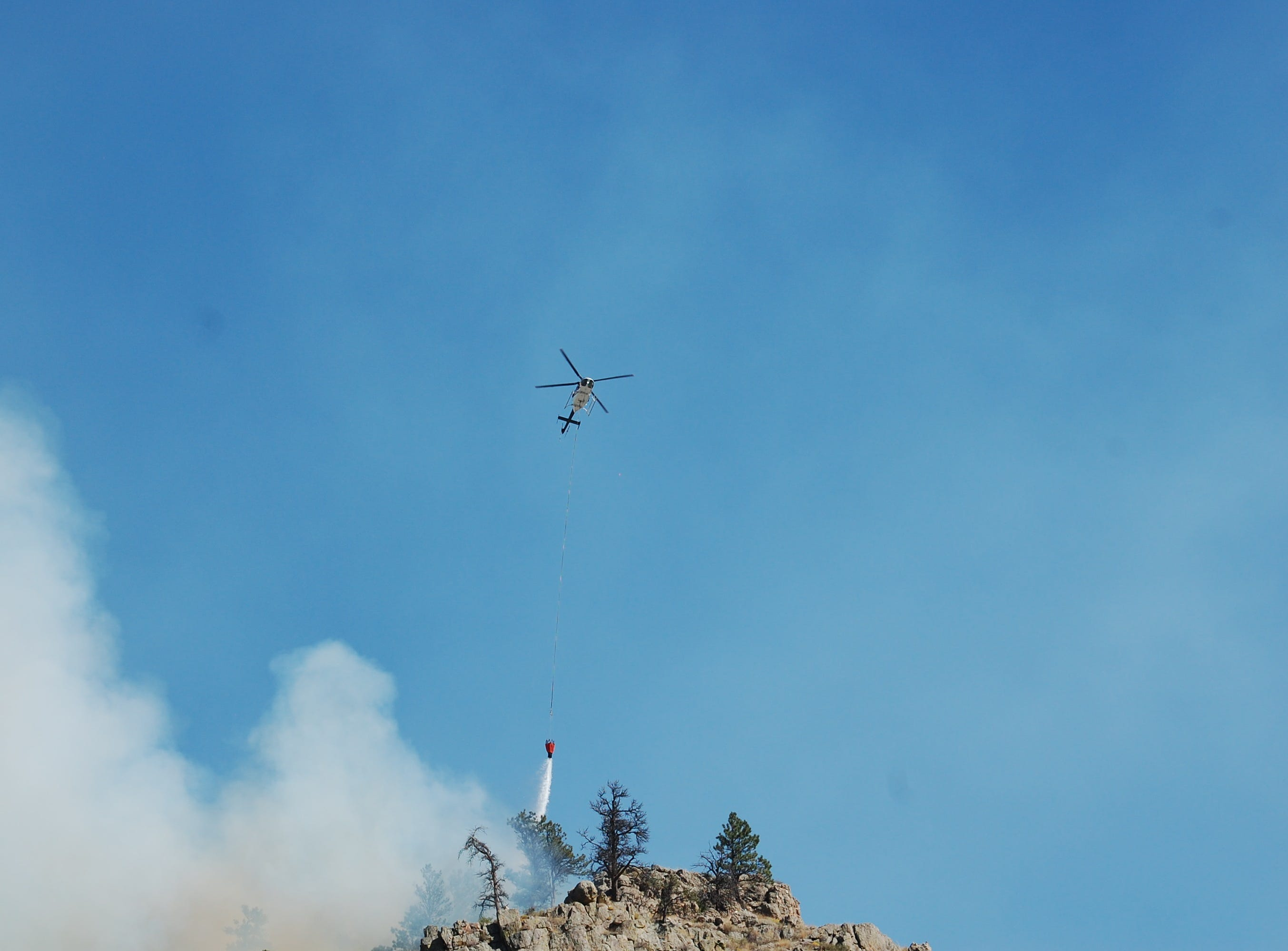 A helicopter drops water on the Seaman Fire just west of Gateway Park and north of Colorado Highway 14 on Wednesday.