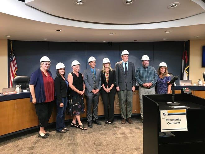 Poudre School District Board of Education members pause to celebrate authorizing bond sales. The vote comes after a two-year delay caused by litigation.
