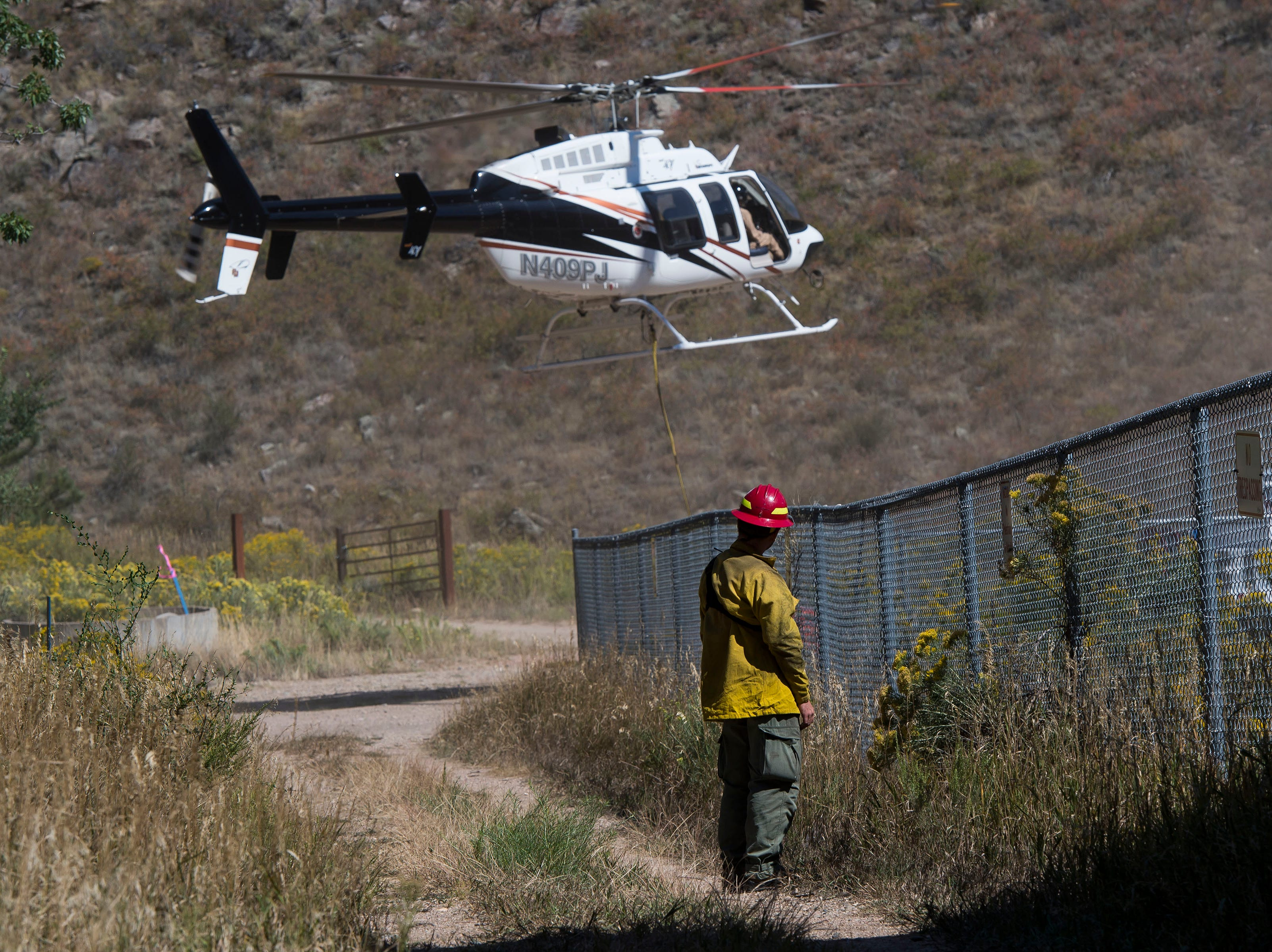 A firefighter looks on as a helicopter takes off from the staging area in Gateway Park on Wednesday, Sept. 12, 2018, in the Poudre Canyon, near Seaman Reservoir in Larimer County, Colo.