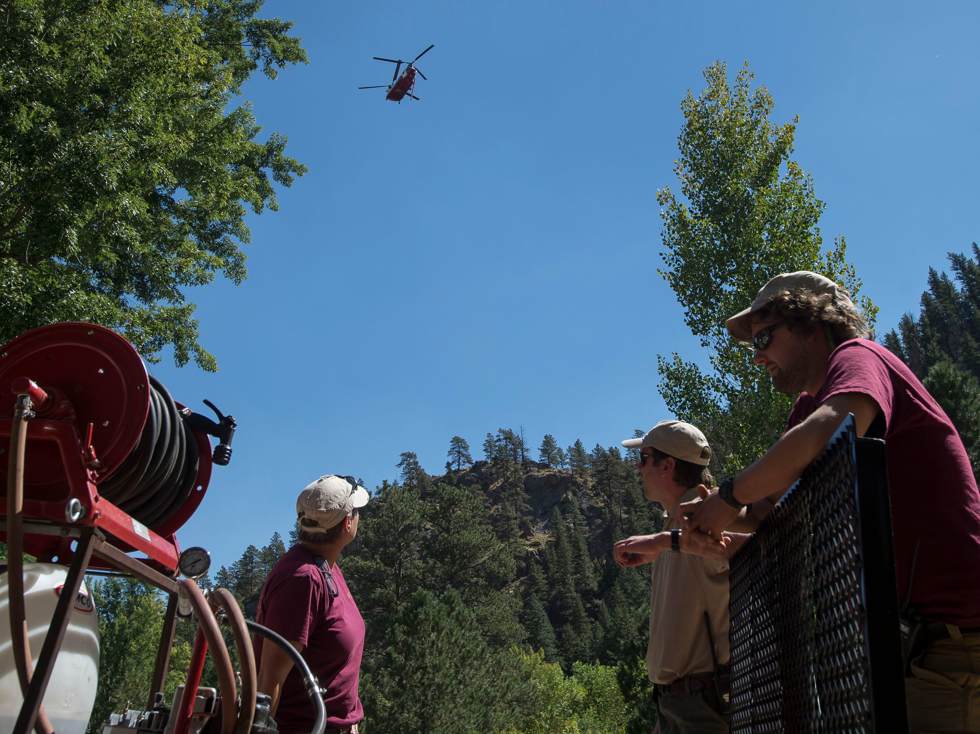 Gateway Park resident Park Ranger Gabe Johnson, center, and City of Fort Collins Natural Area crew members Peter Garner, right, and Anastasia Patterson, left, look up as a large tandem rotor helicopter carries water from Seaman reservoir to the fire nearby on Wednesday, Sept. 12, 2018, at Gateway Park in Larimer County, Colo.