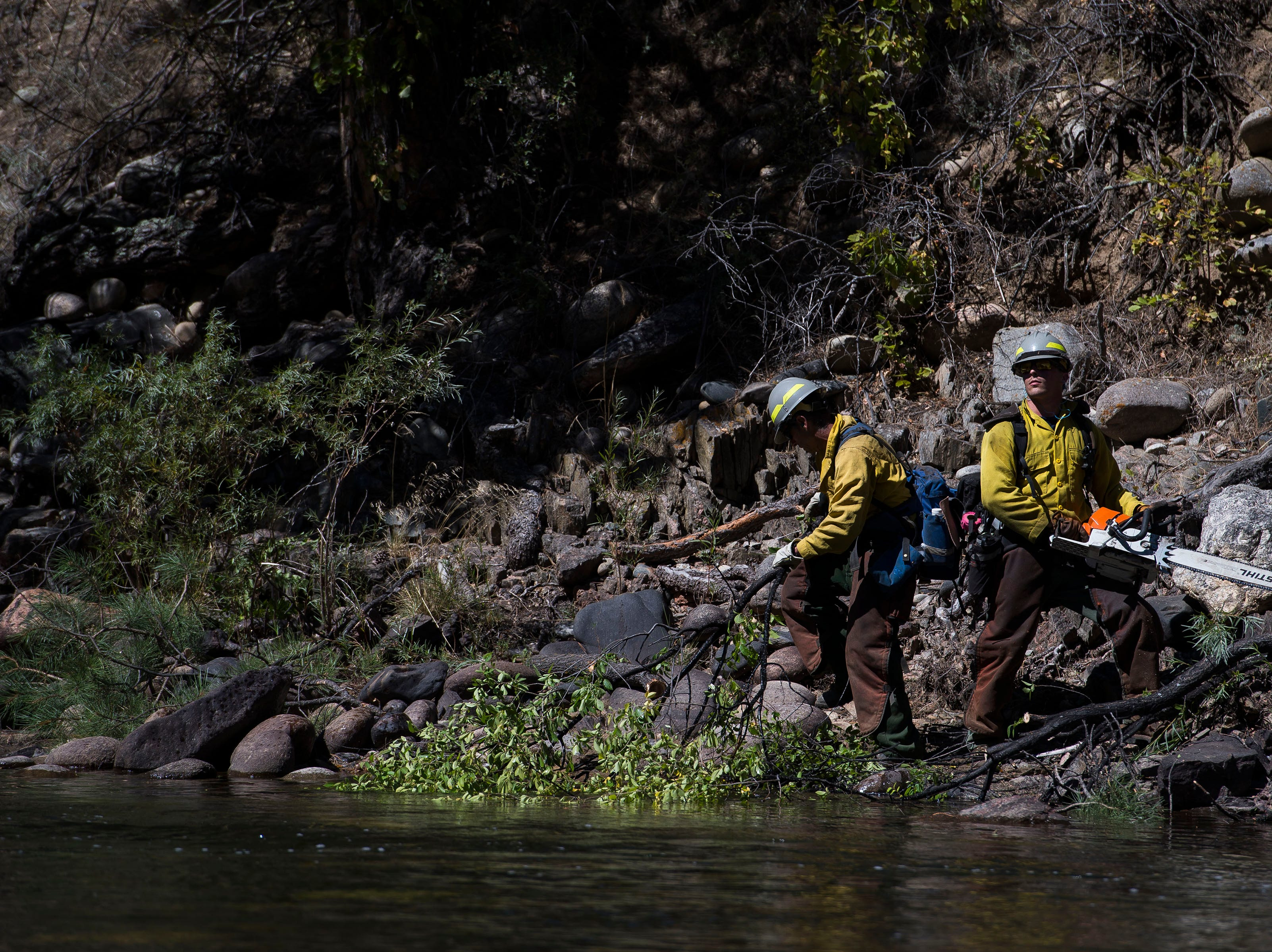 Backcountry firefighters cut down trees near the banks of the Cache la Poudre River on Wednesday, Sept. 12, 2018, in the Poudre Canyon, near Seaman Reservoir in Larimer County, Colo.