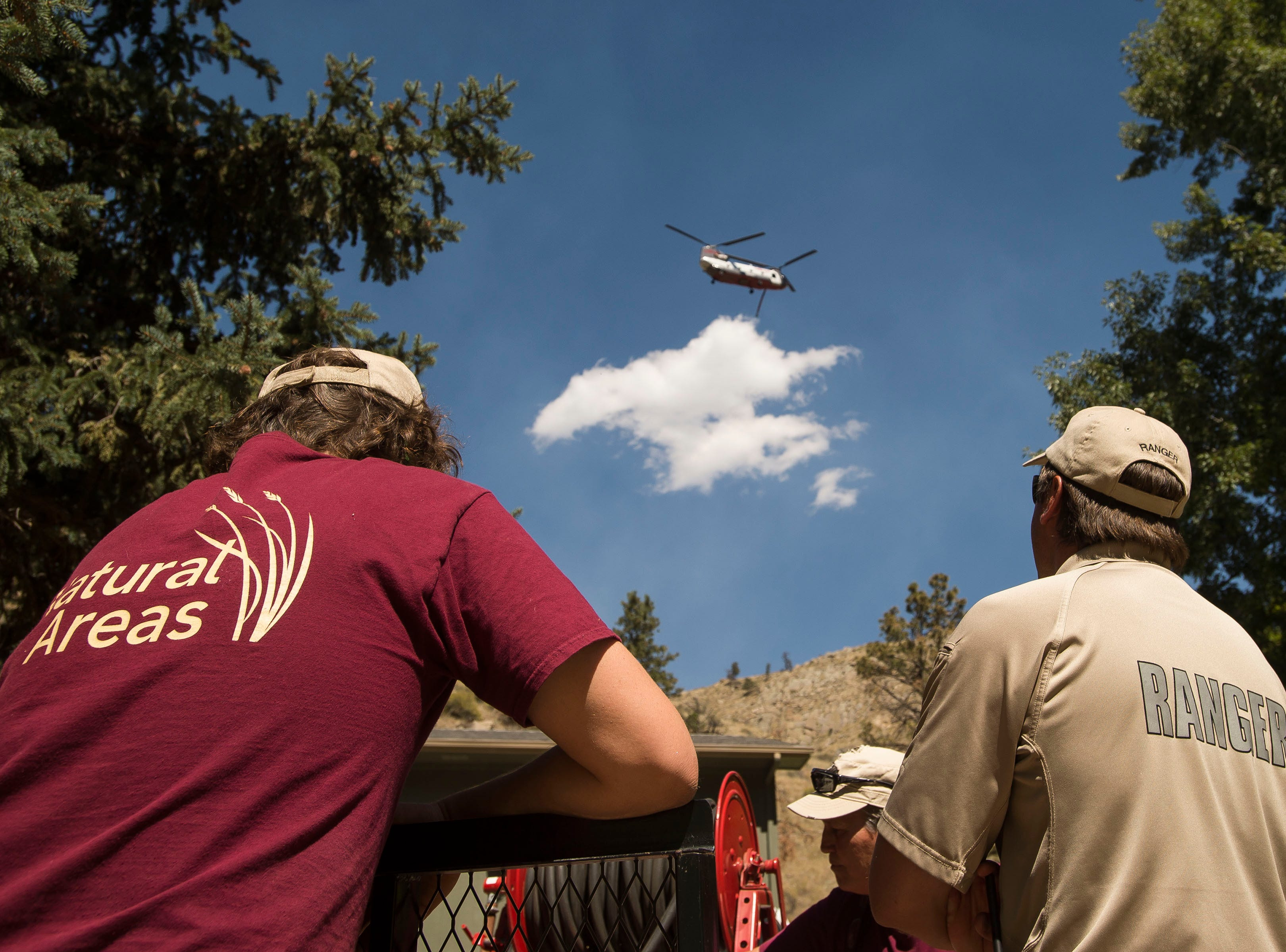 Gateway Park resident Park Ranger Gabe Johnson, right, and City of Fort Collins Natural Area maintenance crew member Peter Garner look up as a large twin rotor helicopter carries water from Seaman reservoir to the fire nearby on Wednesday, Sept. 12, 2018, at Gateway Park in Larimer County, Colo.