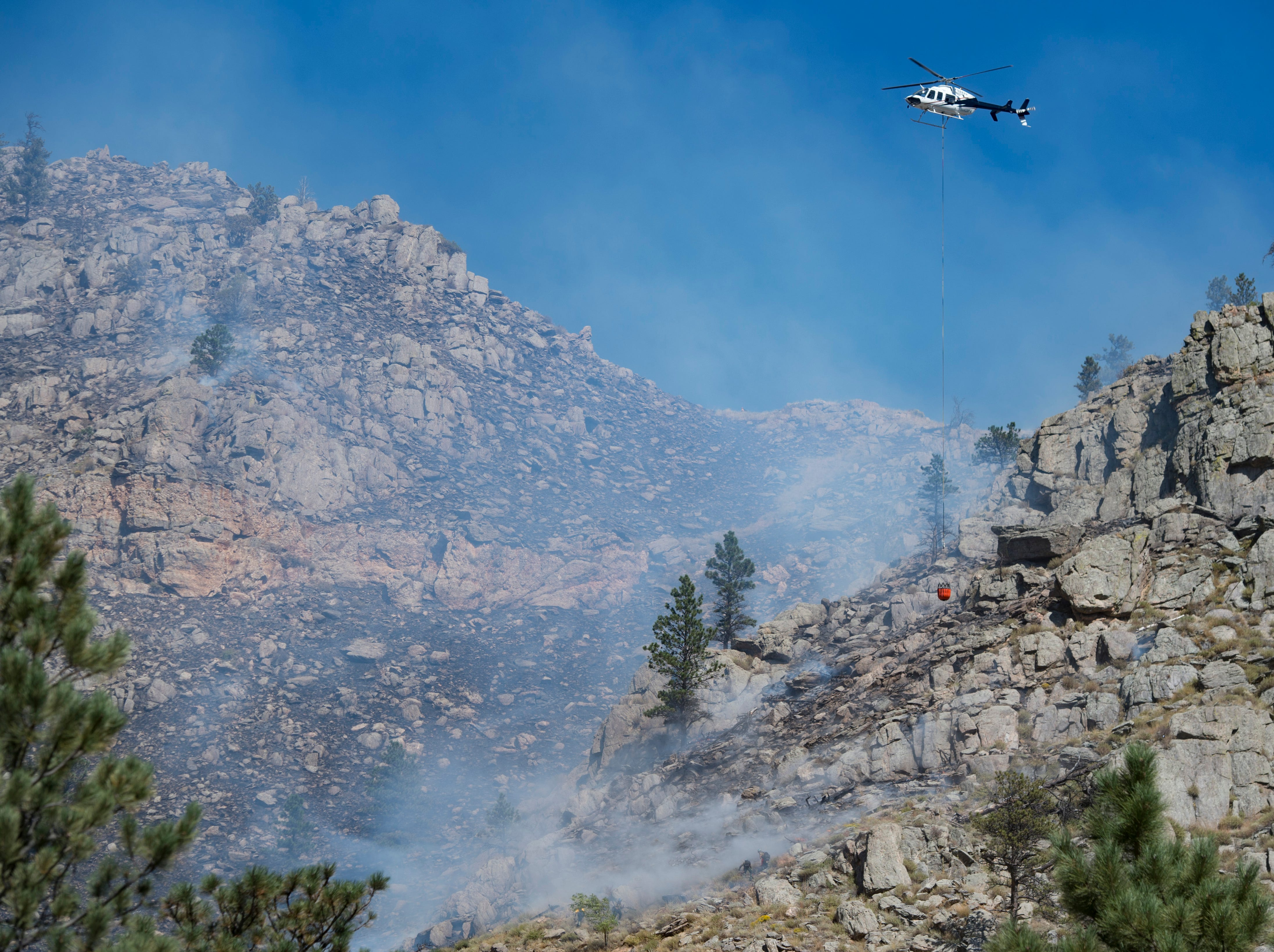A helicopter prepares to make a water drop as firefighters work to contain a blaze in Poudre Canyon west of Seaman Reservoir on Tuesday, September 12, 2018.