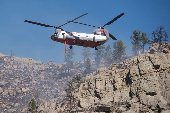 A tandem rotor helicopter prepares to make a water drop as firefighters work to contain a blaze in Poudre Canyon west of Seaman Reservoir on Tuesday, September 12, 2018.