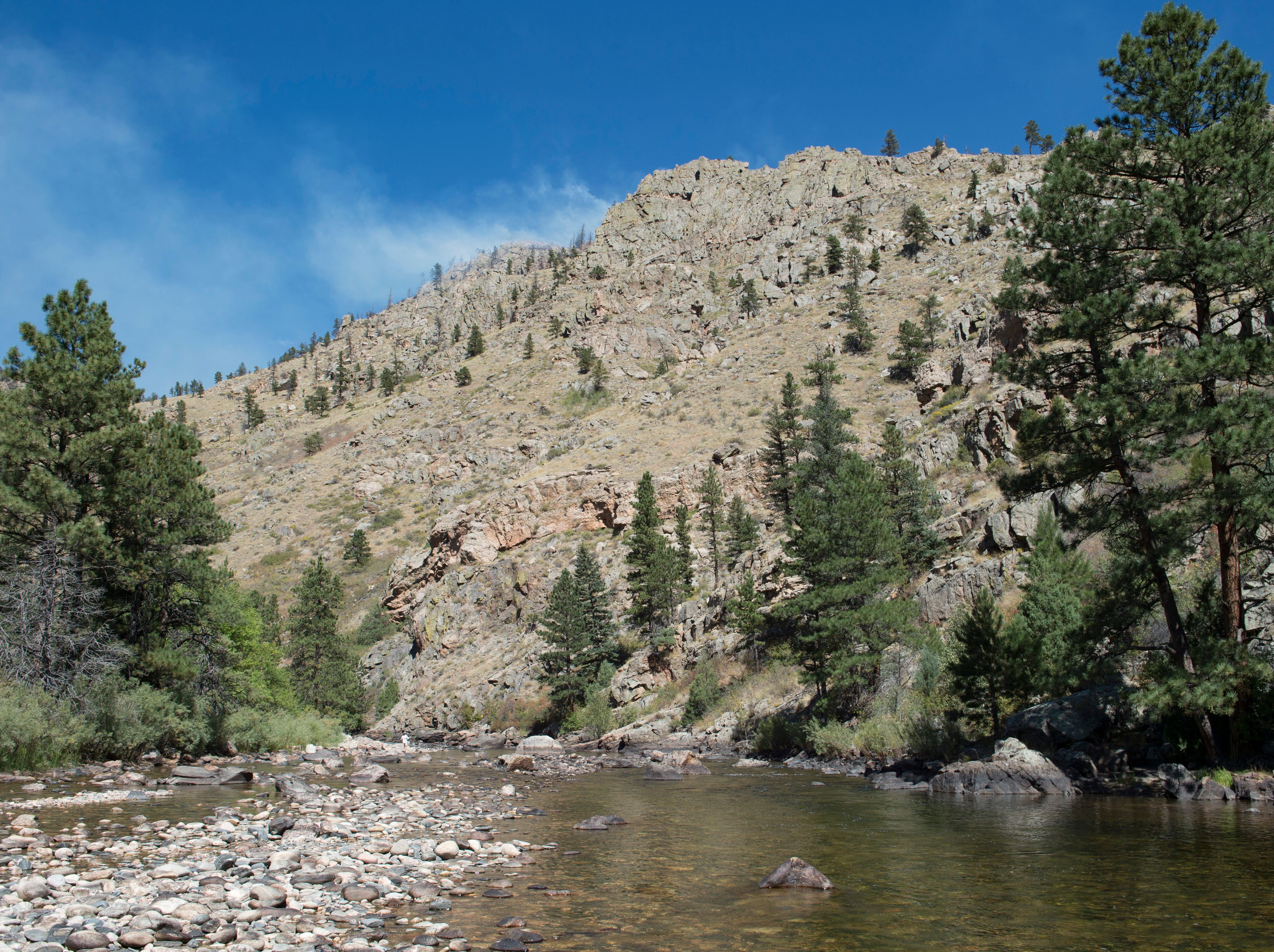 Smoke rises from a ridge above the Poudre River as a fire burns in Poudre Canyon west of Seaman Reservoir on Tuesday, September 12, 2018.