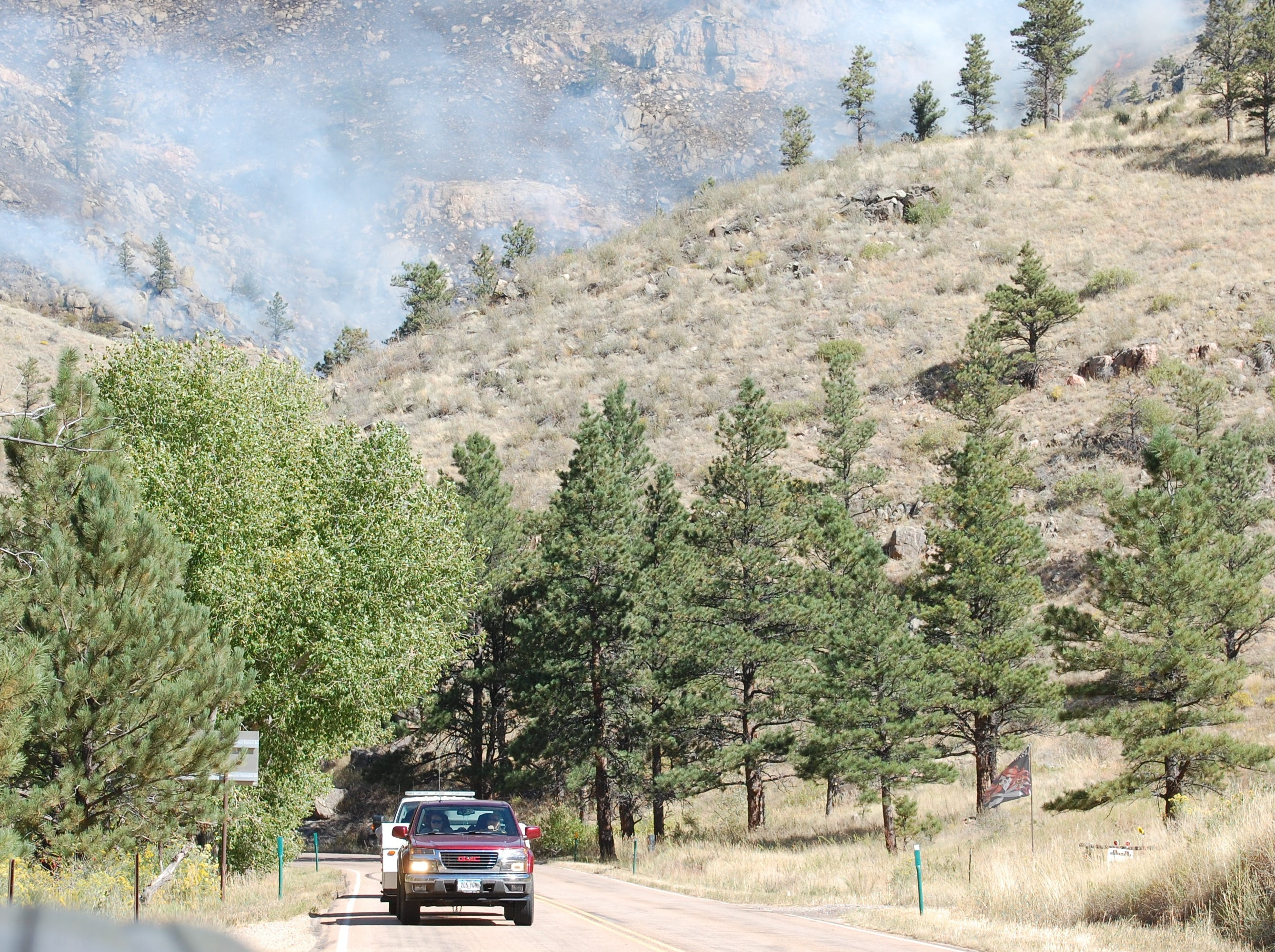 Vehicles drive on Colorado Highway 14 with smoke from the Seaman Fire in the background on Wednesday.