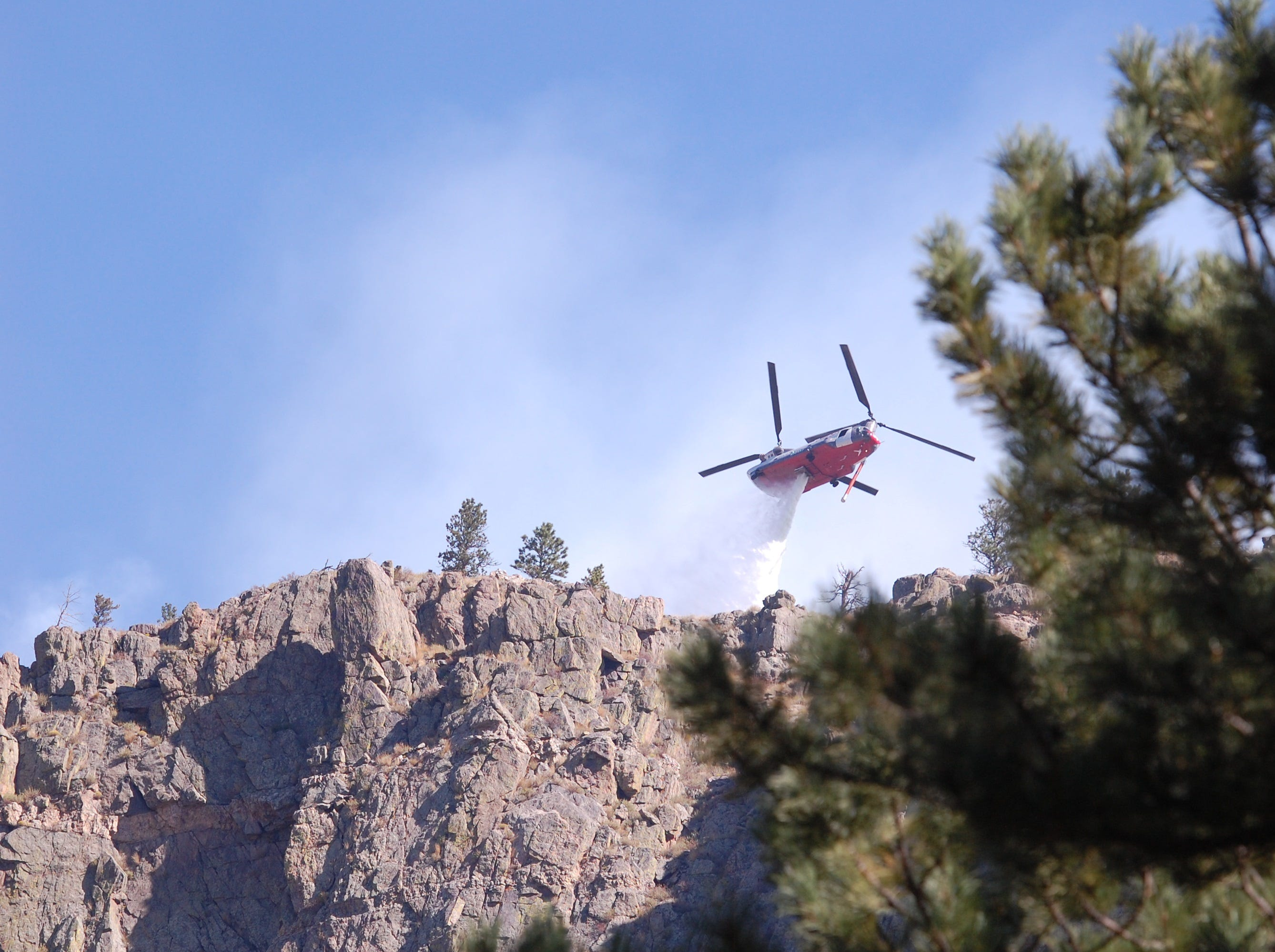 A helicopter drops water on the Seaman Fire above homes on Smith Bridge just west of Gateway Park in Poudre Canyon on Wednesday morning.