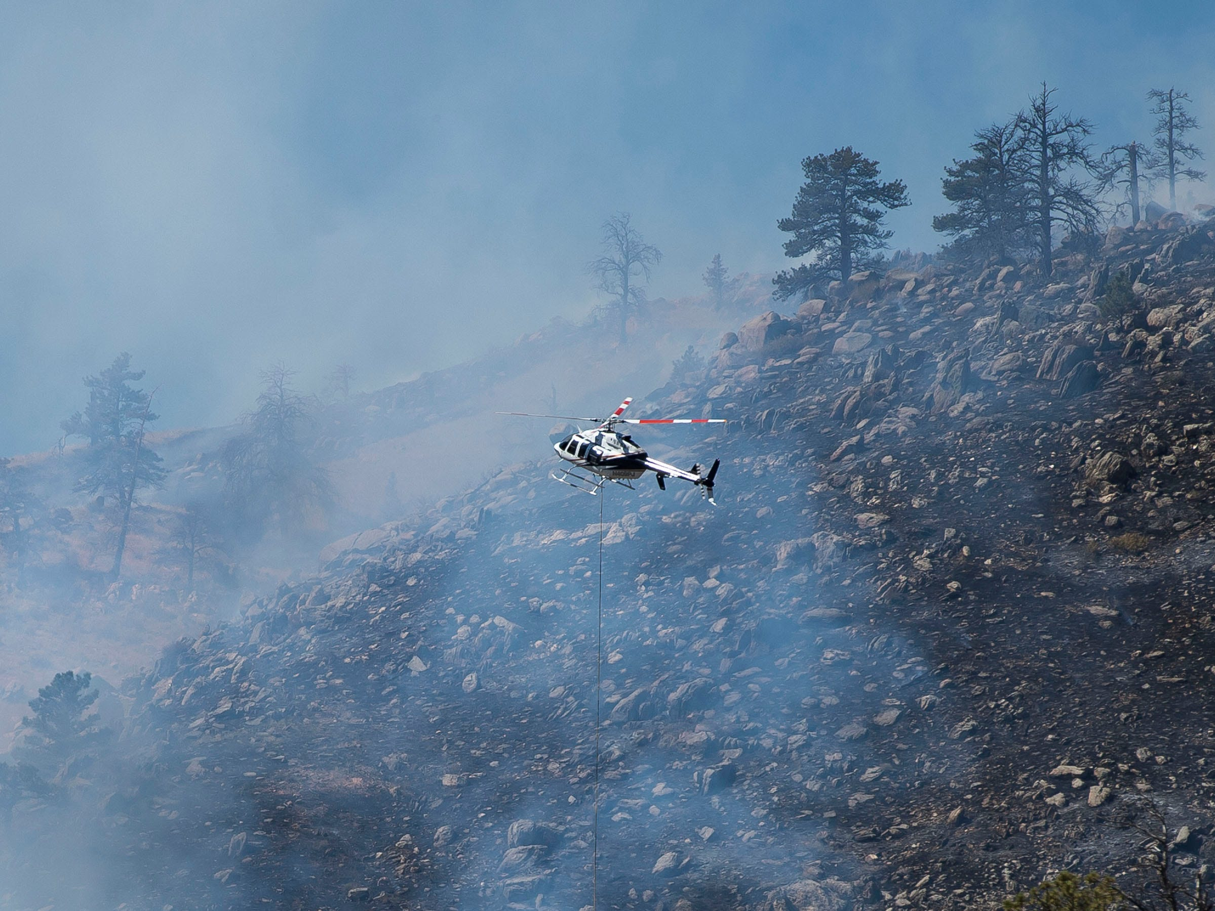 A helicopter drops water from Seaman Reservoir onto the fire burning on the hillside nearby on Wednesday, Sept. 12, 2018, in the the Poudre Canyon, near Seaman Reservoir in Larimer County, Colo.