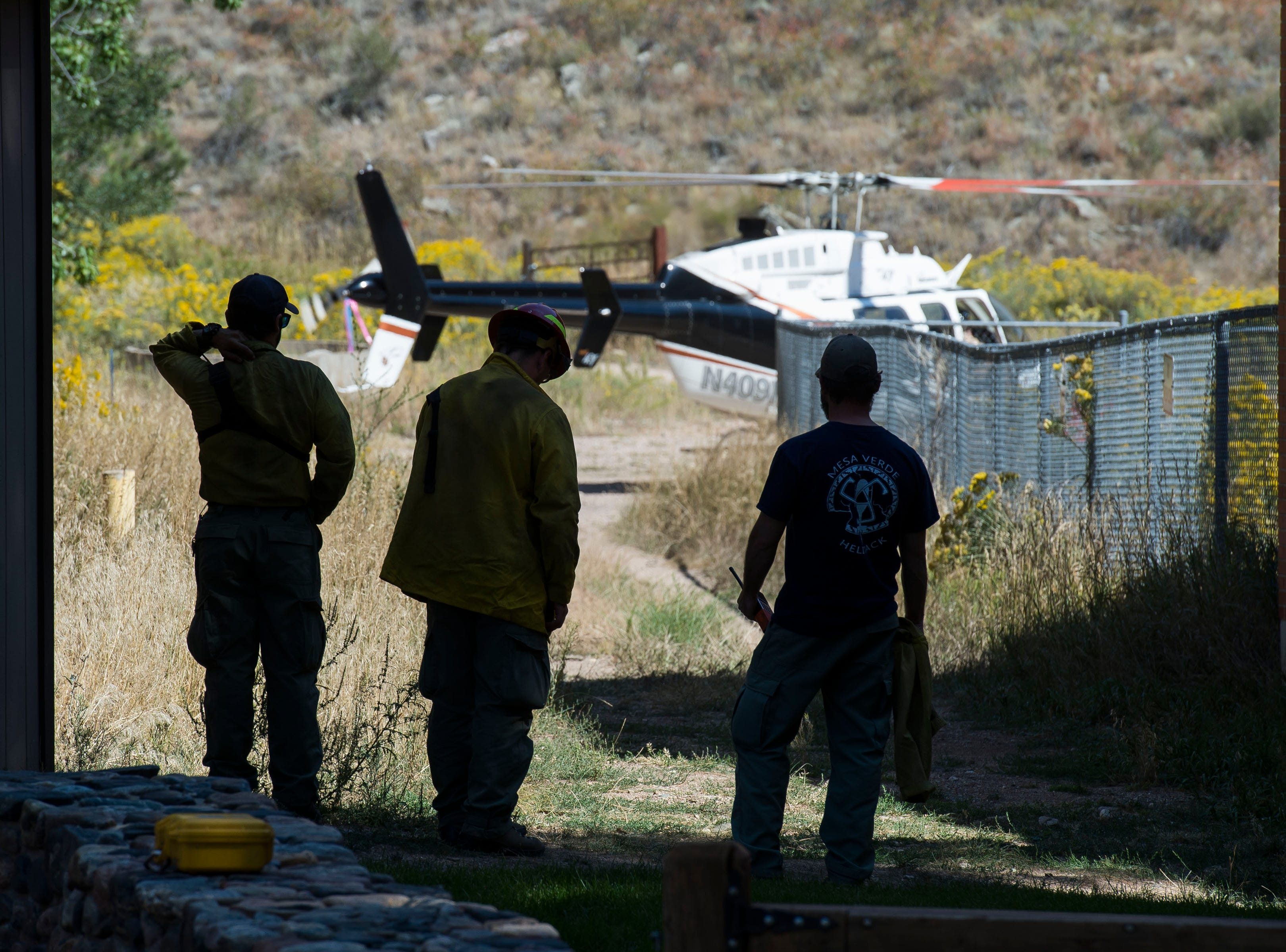 Firefighters look on as a helicopter pulling water from Seaman Reservoir lands at Gateway Park on Wednesday, Sept. 12, 2018, in the Poudre Canyon, near Seaman Reservoir in Larimer County, Colo.