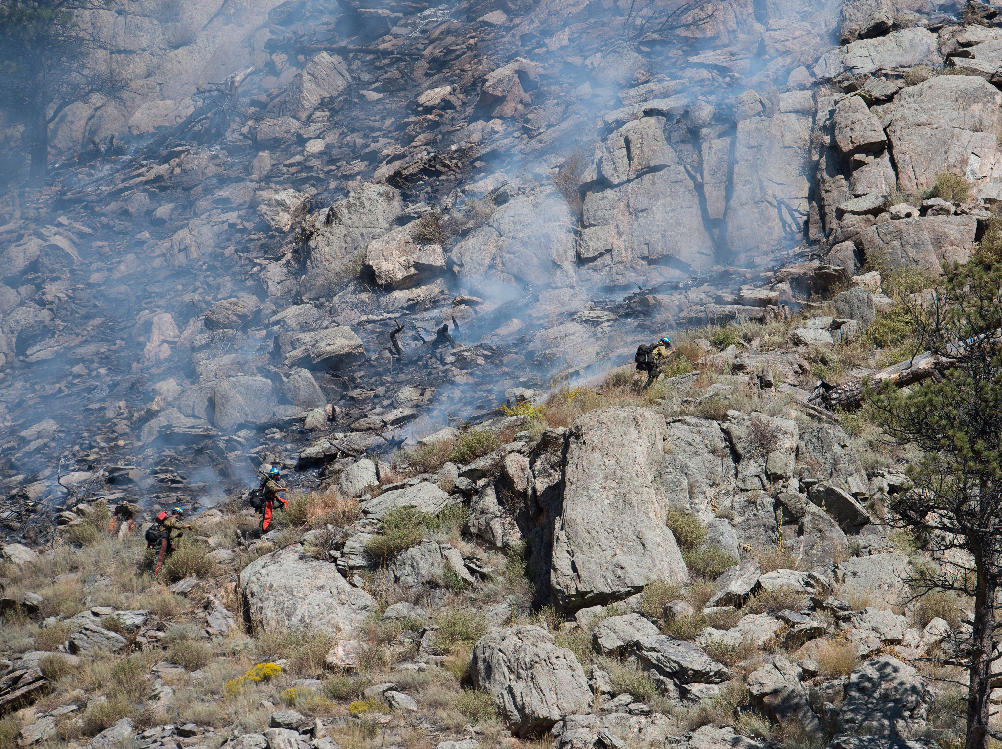 Wildland firefighters climb a ridge on fire to contain a blaze in Poudre Canyon west of Seaman Reservoir on Tuesday, September 12, 2018.