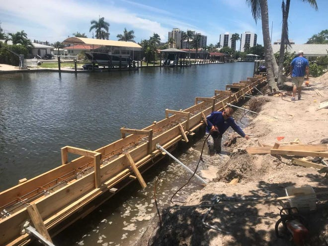Stokes Marine crew members work on repairing a sea wall in Cape Coral. The city have given 251 permits for new sea walls since Hurricane Irma.