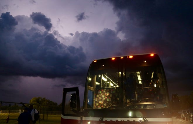Lightning illuminates the clouds over Lehigh Senior as the Sebring football team packs up its bus on Tuesday, Sept. 11, 2018. Storms erased the scheduled game for the second time this season.