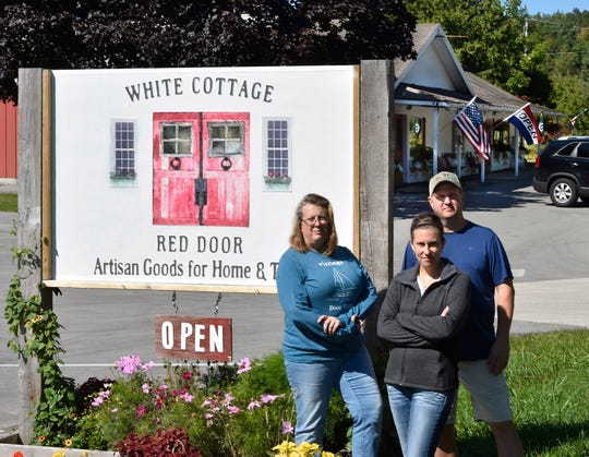 """White Cottage Red Door owners Kevin and Lisa Howard, back, along with Jessica Hadraba, front, and husband Chris Hadraba, not pictured, are challenging town of Gibraltar's ordinance ban on food trucks. Their new food truck was parked next to the retail store at 8813 State 42, just south of Fish Creek, serving """"all things cherry.''"""