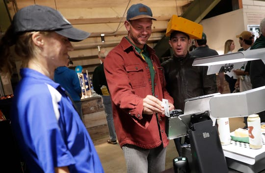 Derek Boyle of Atlantic Mine, Mich., center, and Steve Christinson of London, England, use a video scanner at a new Lambeau Field concession stand during the Green Bay Packers-Chicago Bears game on Sept. 9, 2018.