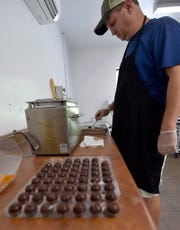 Chocolatier Kevin Howard creates pistachio-rolled truffles Monday inside its commercial kitchen at the White Cottage Red Door, 8813 State 42, in the town of Gibraltar.