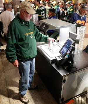 A fan buys beer using a video scanner at one of the grab-and-go concession stands at Lambeau Field during the Green Bay Packers-Chicago Bears game on Sept. 9, 2018.