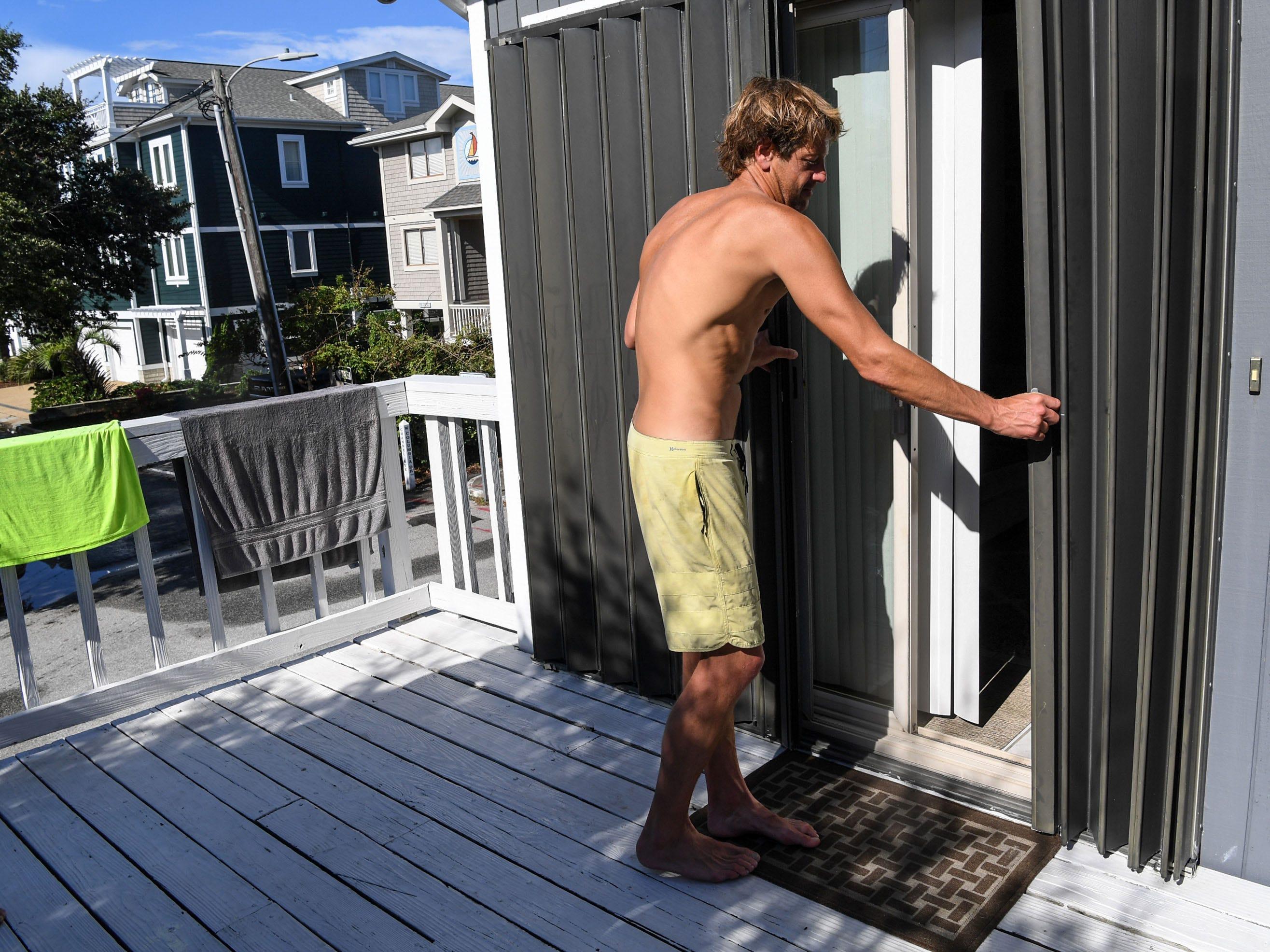 Austin Parker slides hurricane shutters at his apartment at Wrigtsville Beach in Wilmington, North Carolina on Wednesday, September 12, 2018.  (Ken Ruinard / Greenville News / Gannett USA Today Network / 2018 )