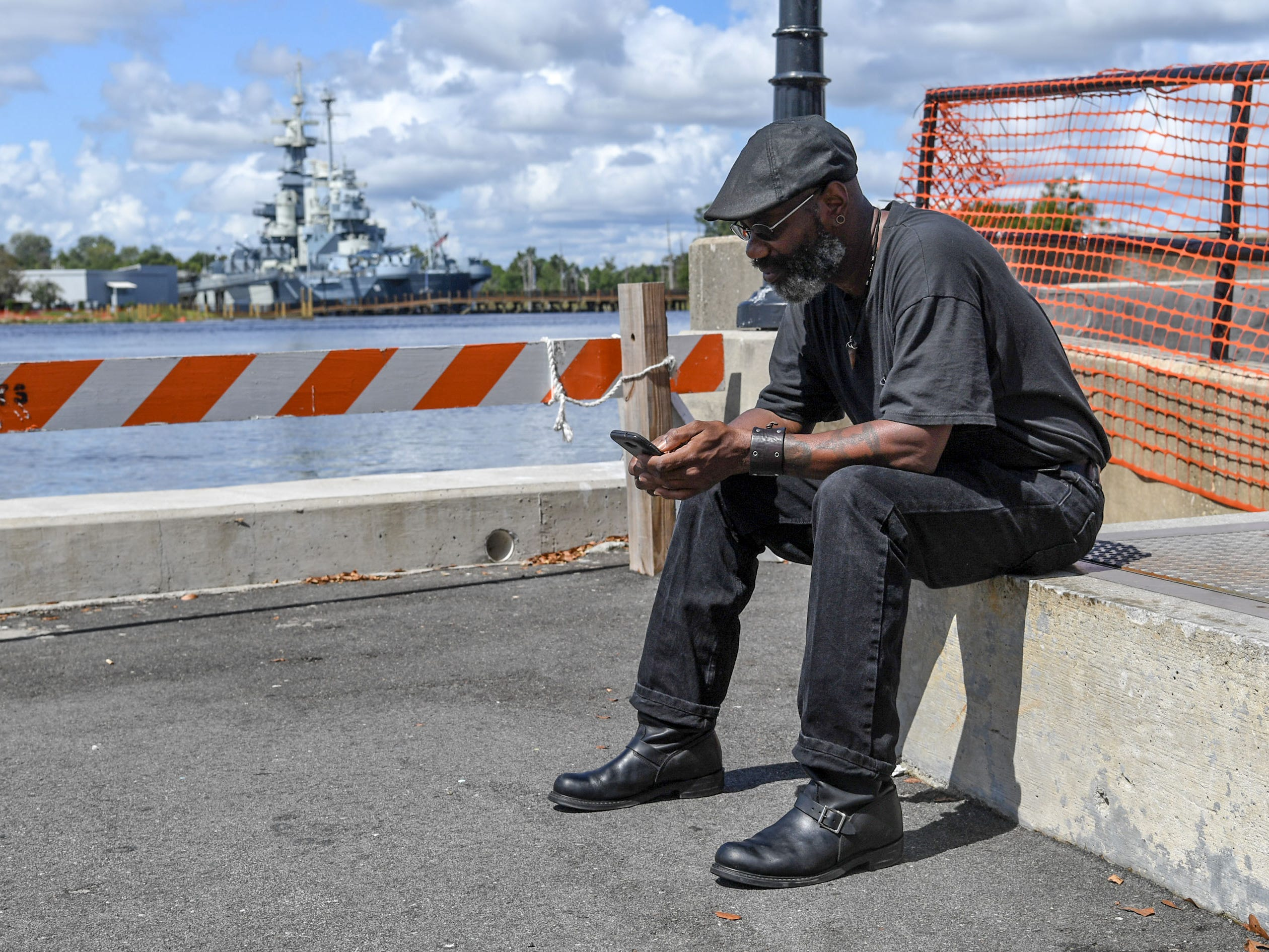James Walker looks at his iPhone while taking time off from his shipyard job at the port of Wilmington, sitting near the USS North Carolina in Wilmington, North Carolina on Wednesday, September 12, 2018.  (Ken Ruinard / Greenville News / Gannett USA Today Network / 2018 )