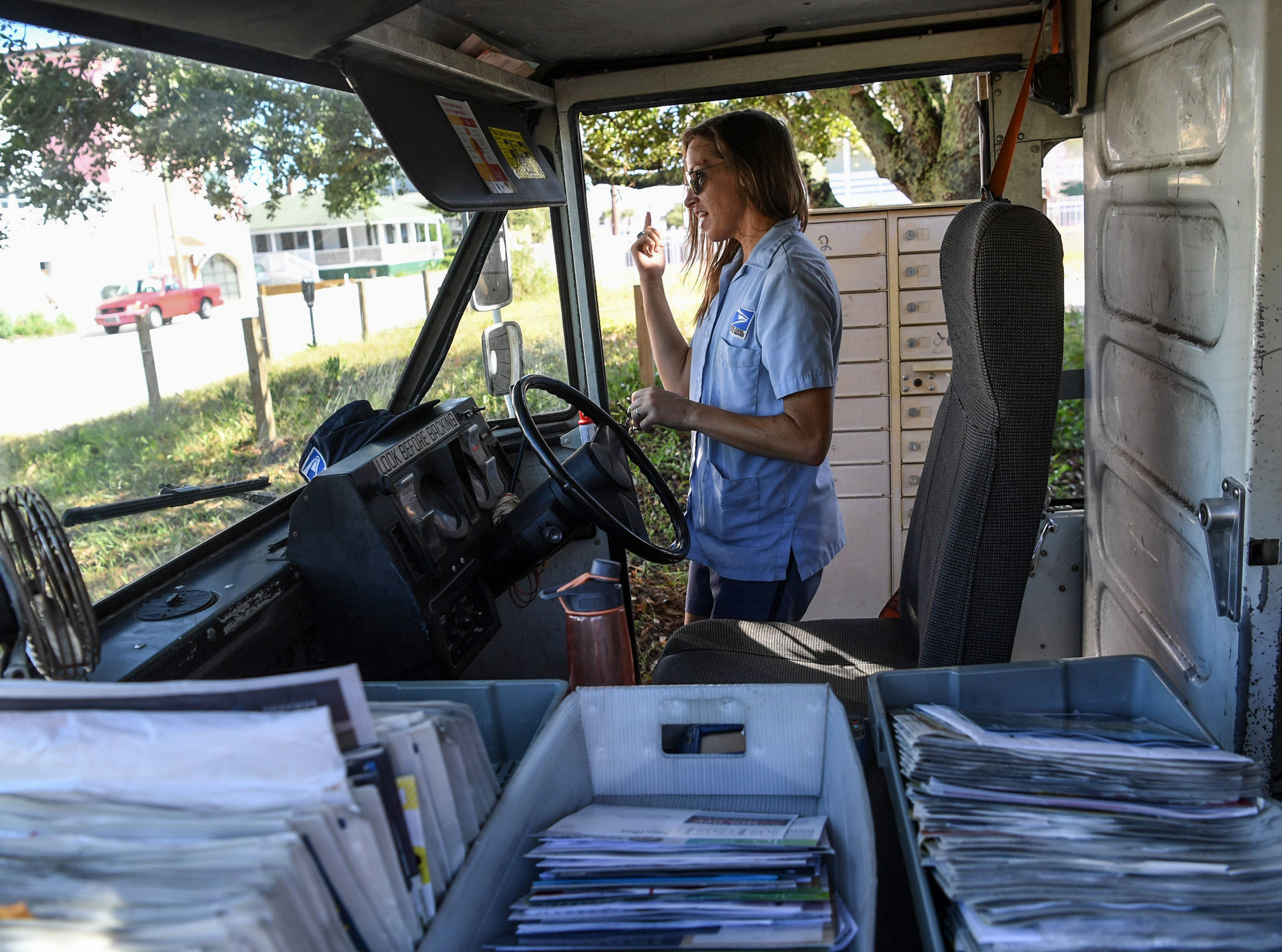 U.S. Postal Carrier Lindsey Fox delivers mail for the last day before Hurricane Florence, at Wrigtsville Beach in Wilmington, North Carolina on Wednesday, September 12, 2018.  (Ken Ruinard / Greenville News / Gannett USA Today Network / 2018 )