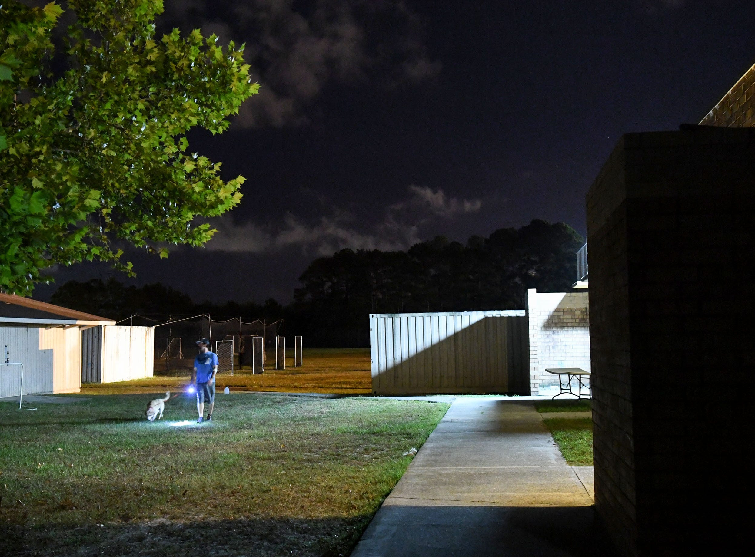 Jameson McDermott, an employee with New Hanover County, takes a dog for a walk at the county emergency shelter held at Trask Middle School in Wilmington, North Carolina on Tuesday, September 11, 2018. Hurricane Florence is expected to make landfall in Wilmington Thursday night. (Ken Ruinard / Greenville News / Gannett USA Today Network / 2018 )
