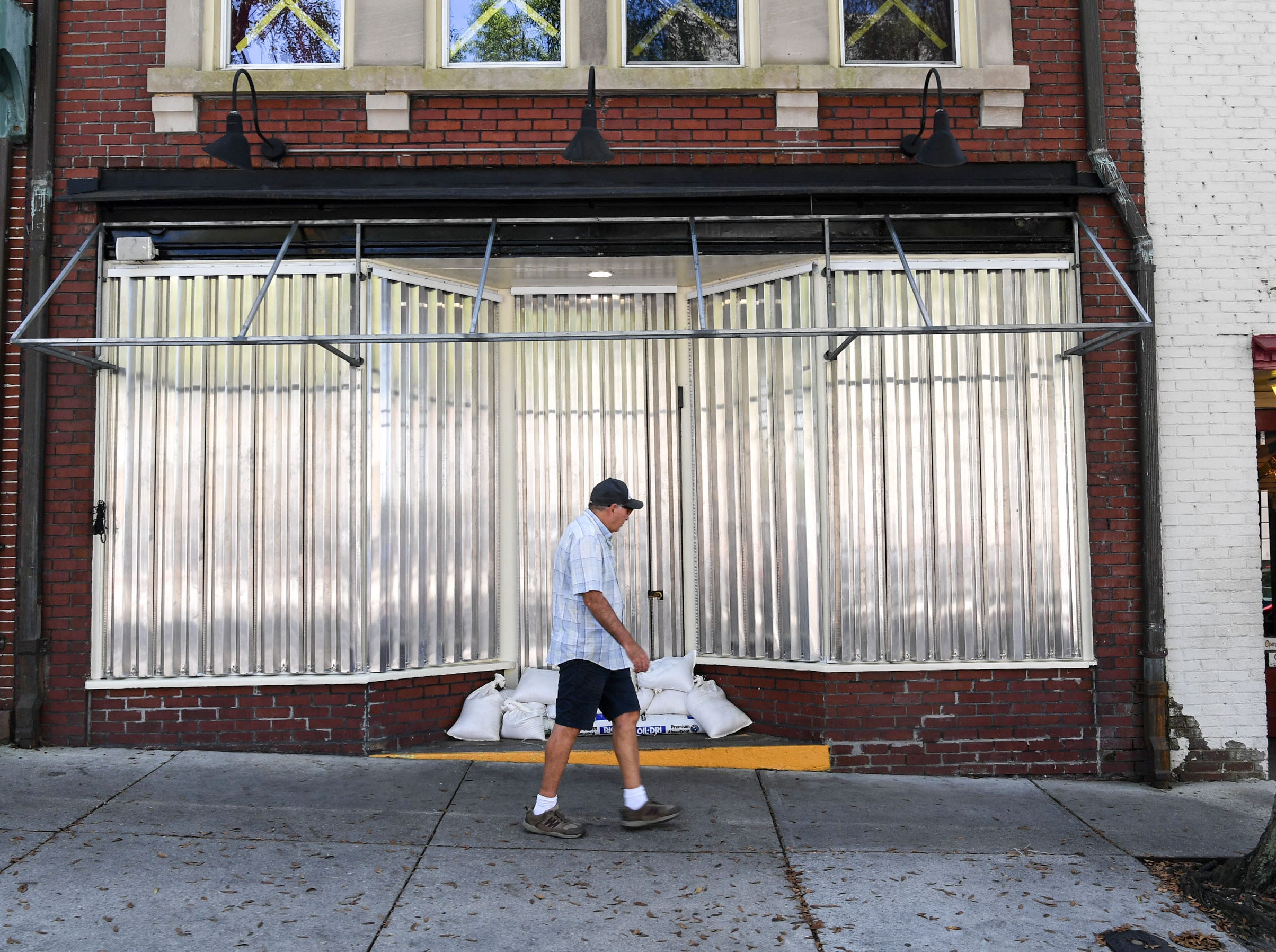 David Lant walks by a restaurant with a metal window protector near the riverfront in Wilmington, North Carolina on Wednesday, September 12, 2018.  (Ken Ruinard / Greenville News / Gannett USA Today Network / 2018 )
