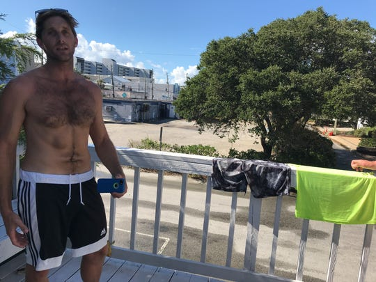 Austin Heffner, of Wilmington, N.C., plans to ride out the storm, then surf in its wake.