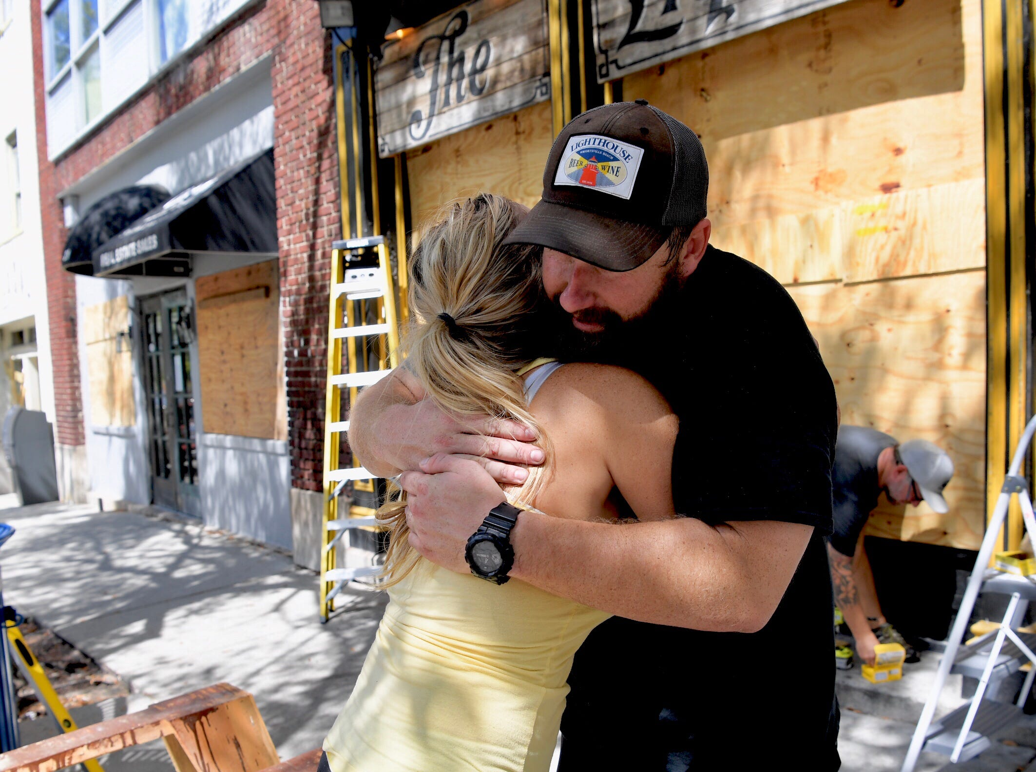 Jennifer Wilson hugs former Liquid Room employee Andy Correll as they prepare for Hurricane Florence in Wilmington, N.C., on Wednesday, Sept. 12, 2018.