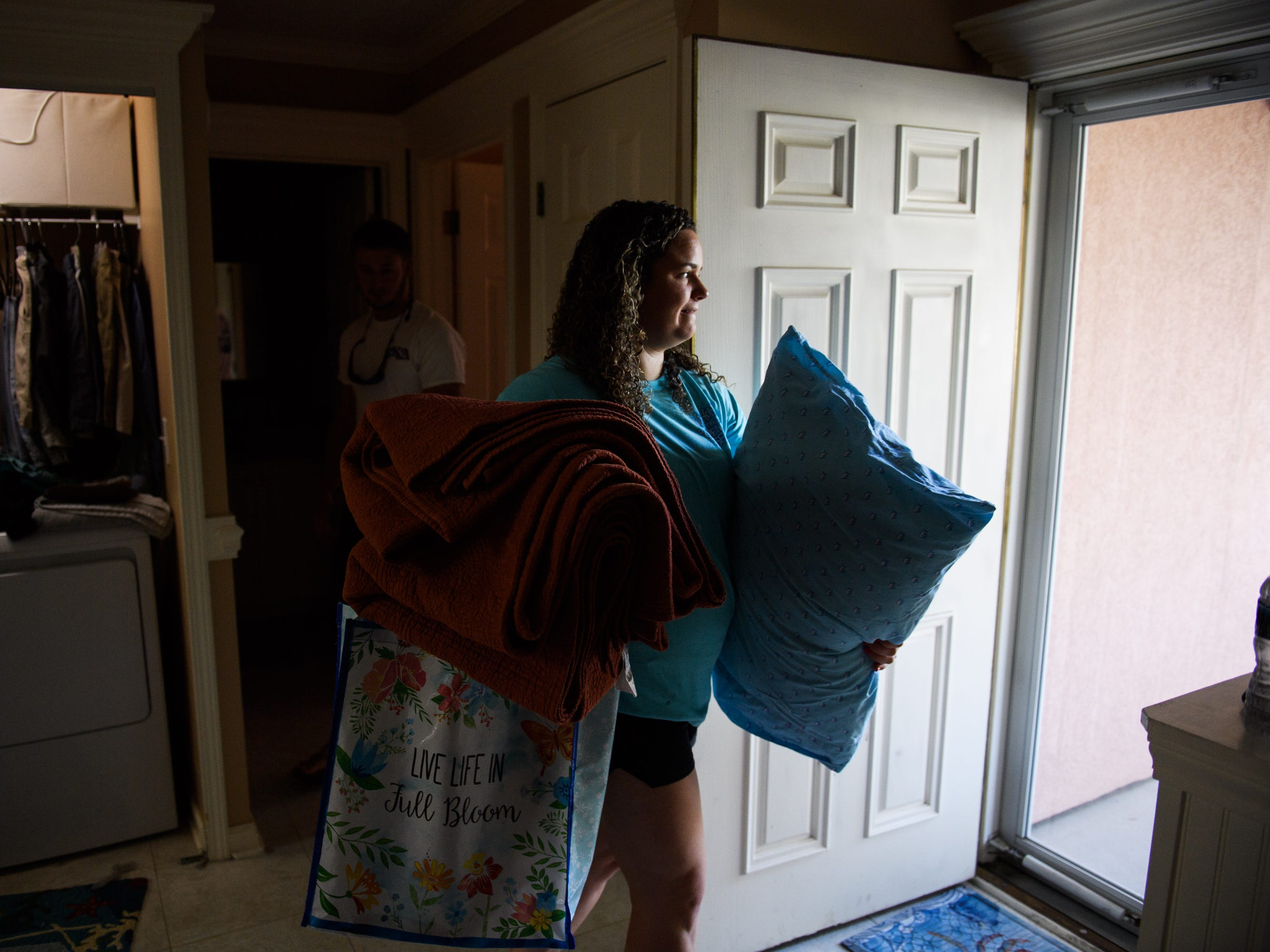 Karly Suggs takes a pillow, towels and other necessities to her car as she prepares to evacuate her North Myrtle Beach home ahead of Hurricane Florence on Wednesday, Sept. 12, 2018.