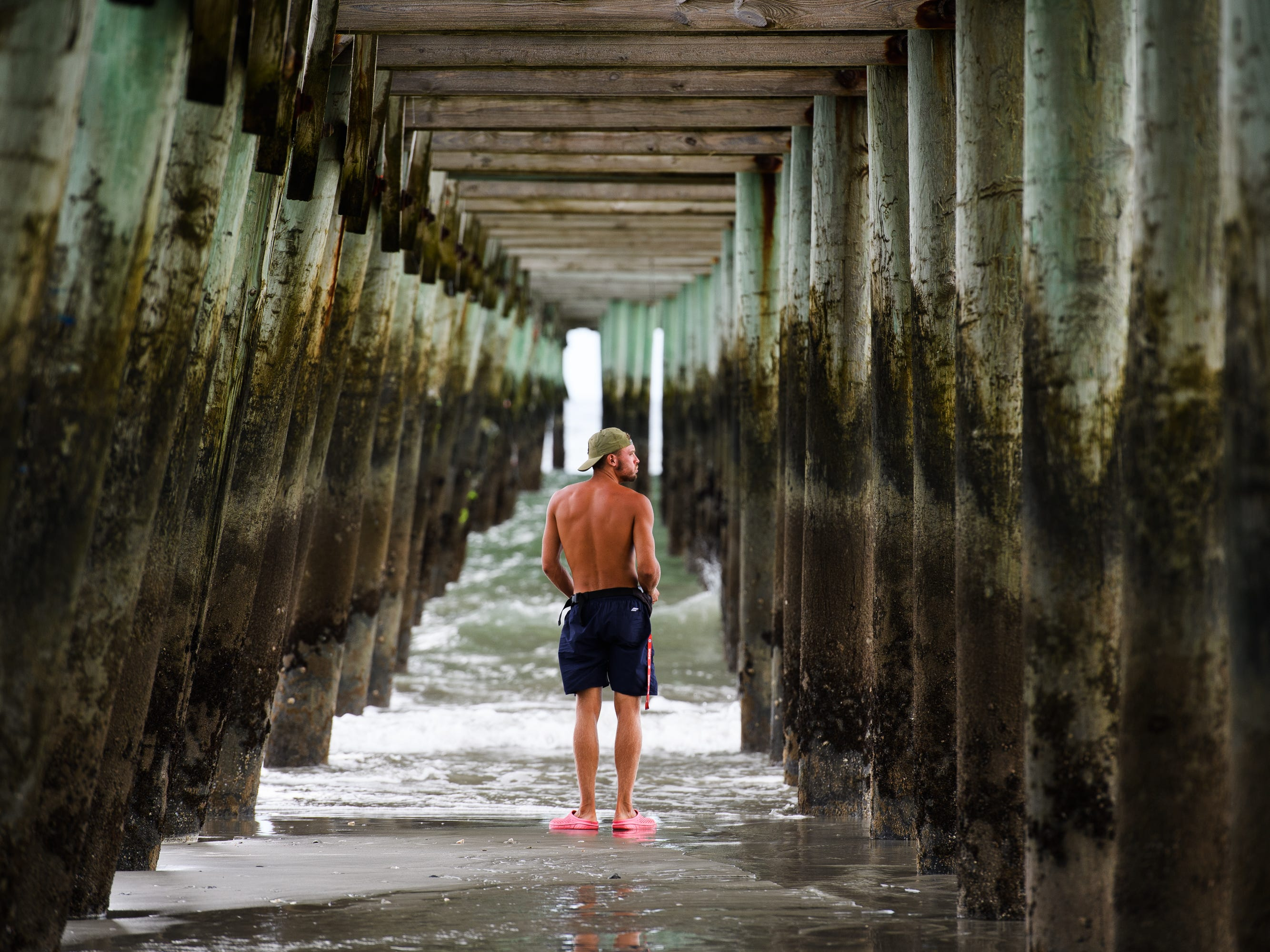 Kamil Korzec walks under the Second Avenue Pier in Myrtle Beach days before Hurricane Florence is expected to hit the coast of North and South Carolina on Tuesday, Sept. 11, 2018.