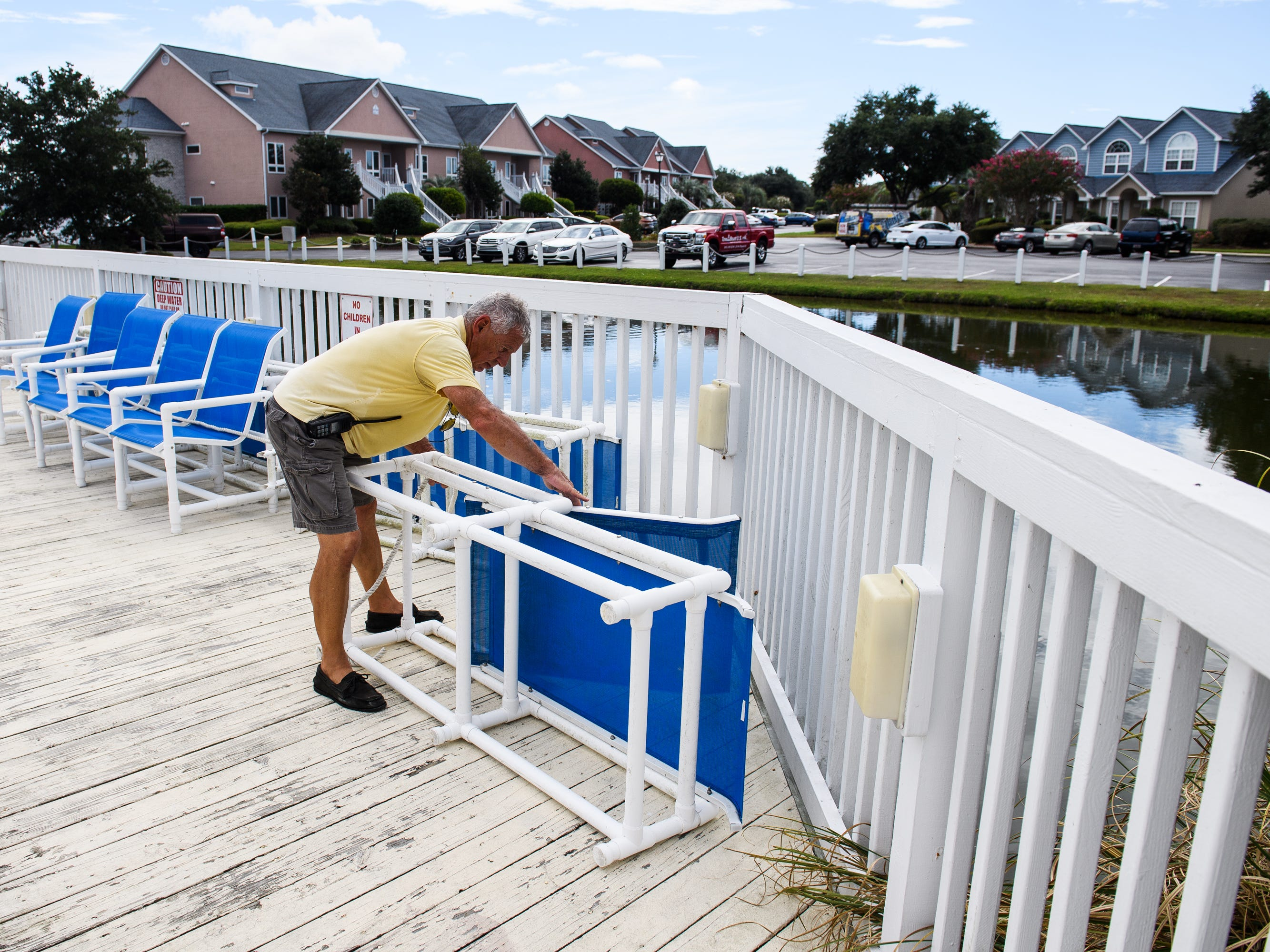 George Rubis, assistant dock manager at the Lightkeepers Marina, ties up sunbathing chairs at the clubhouse on Wednesday, Sept. 12, 2018.