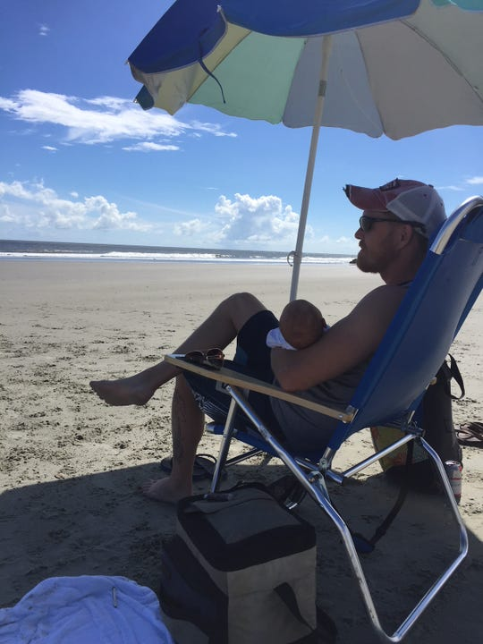 Allen Beasley sits under an umbrella on Folly Beach with his infant, Avery, on Wednesday, September 12, as Hurricane Florence approaches the South Carolina coast.