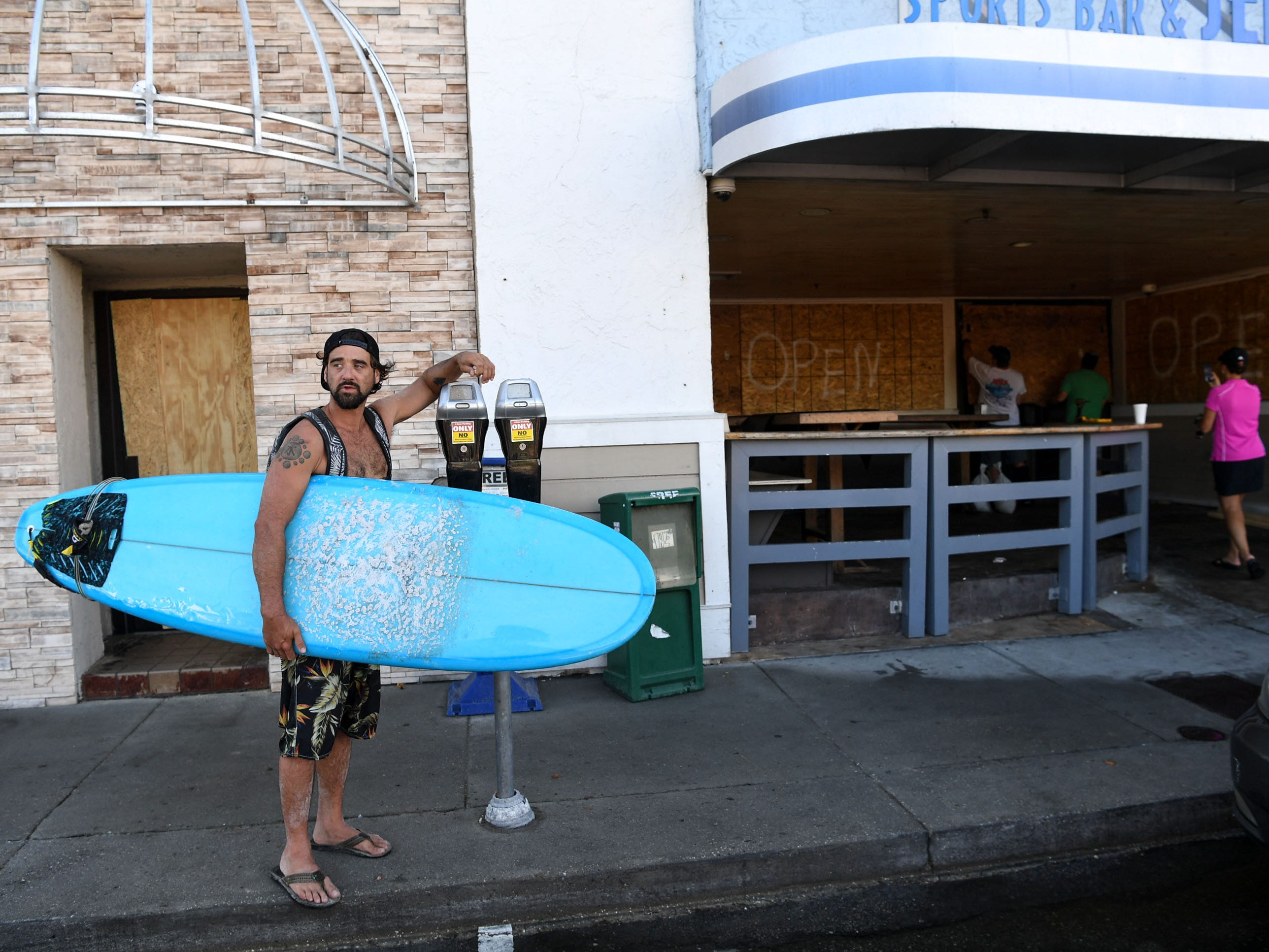 James Waters of Wilmington finished surfing and stopped by to see his friends boarding up Jerry Allen's Grill at Wrigtsville Beach in Wilmington, North Carolina on Wednesday, September 12, 2018.  (Ken Ruinard / Greenville News / Gannett USA Today Network / 2018 )