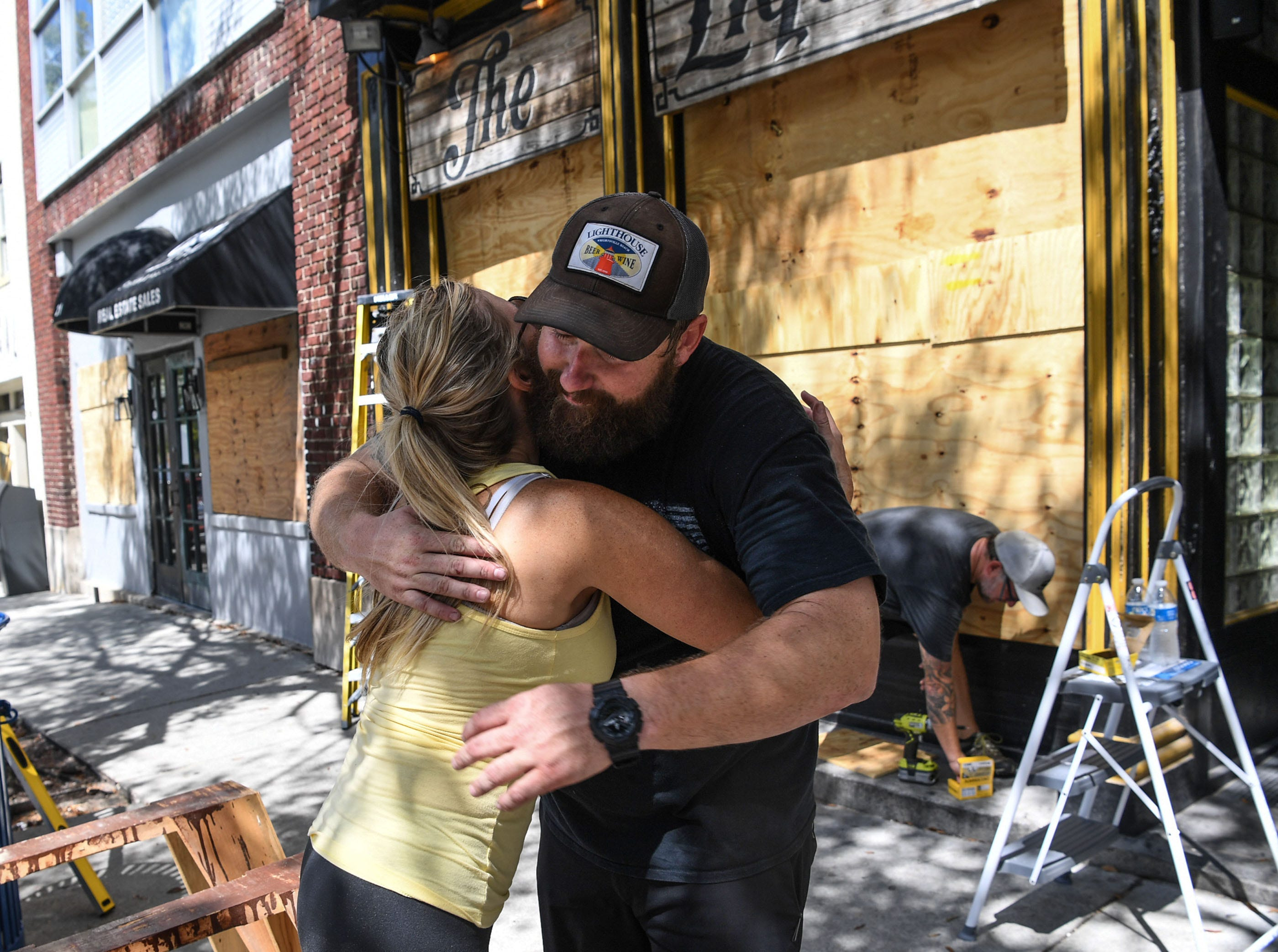 Jennifer Wilson gives a hug to Andy Correll at The Liquid Room, a bar near the riverfront in Wilmington, North Carolina on Wednesday, September 12, 2018.  (Ken Ruinard / Greenville News / Gannett USA Today Network / 2018 )