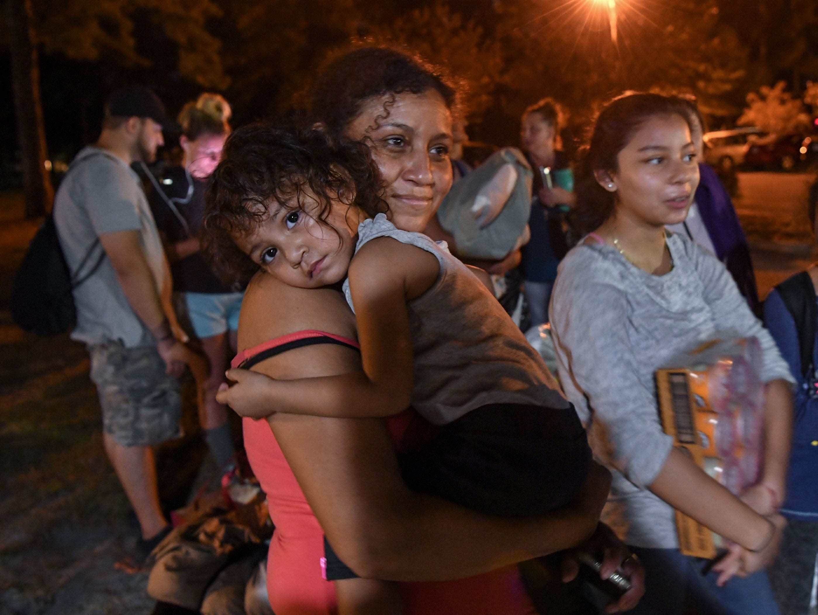 Melba Varbona, holds her daughter Joseline Merlos, right, of Wilmington near her family waiting to check in the New Hanover County emergency shelter at Trask Middle School in Wilmington, North Carolina on Tuesday, September 11, 2018. Hurricane Florence is expected to make landfall in Wilmington Thursday night. (Ken Ruinard / Greenville News / Gannett USA Today Network / 2018 )