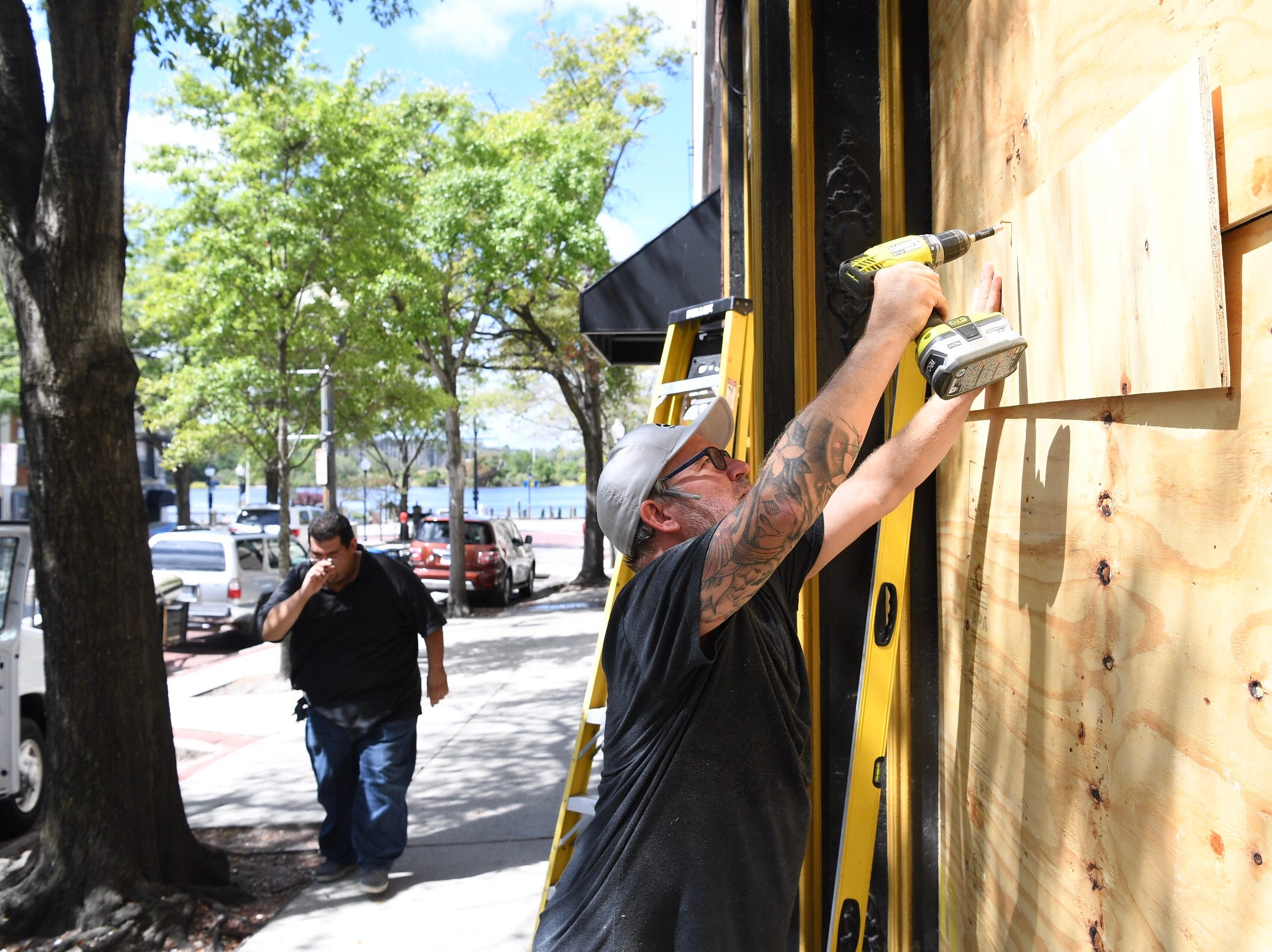 Shawn Booth, owner of The Liquid Room, puts boards on windows of his bar on Market Street in downtown Wilmington, N.C., on Wednesday, Sept. 12, 2018.