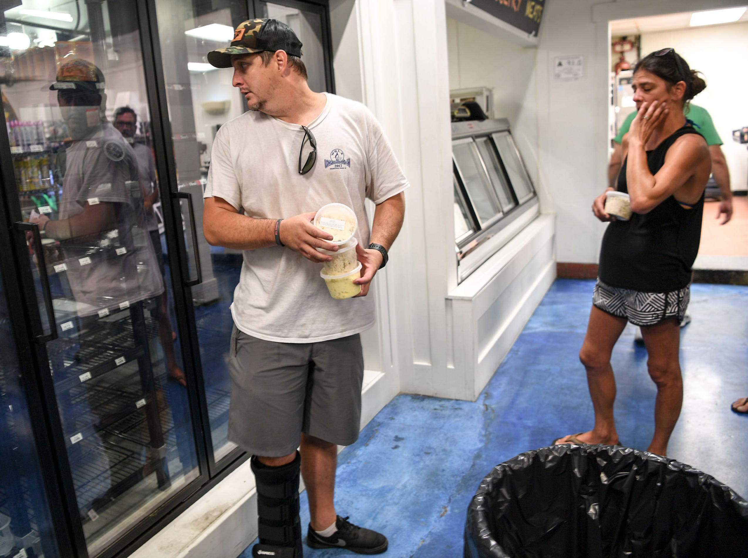 Kelly Baucom, owner of Jerry Allen's Grill, gets prerishable items at Roberts Grocery, at Wrigtsville Beach in Wilmington, North Carolina on Wednesday, September 12, 2018. The store was giving away perishables since they would go to waste. (Ken Ruinard / Greenville News / Gannett USA Today Network / 2018 )