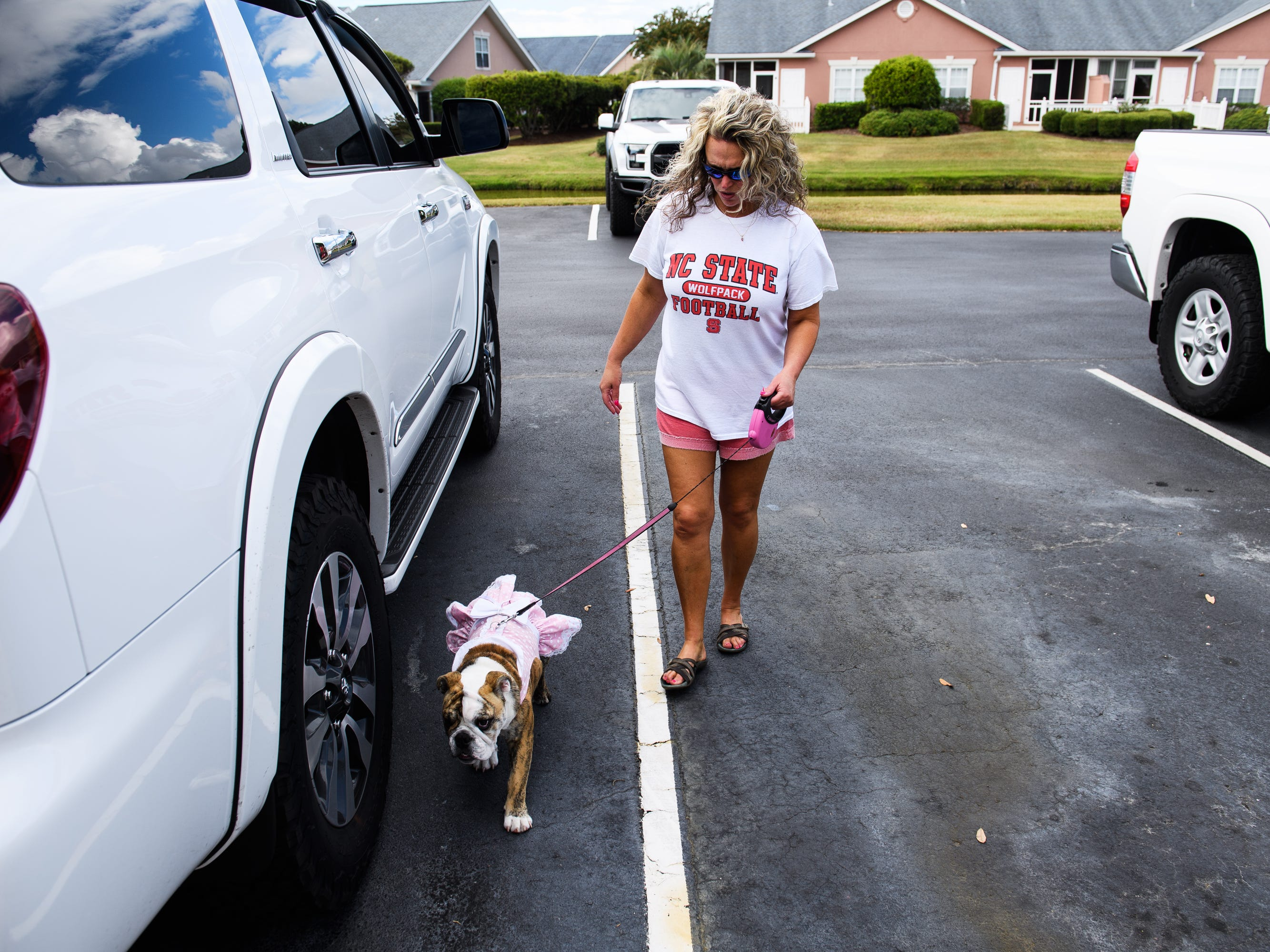 Stacy Prince walks her dog Dixie before she and her husband Billy evacuate their home ahead of Hurricane Florence on Wednesday, Sept. 12, 2018.