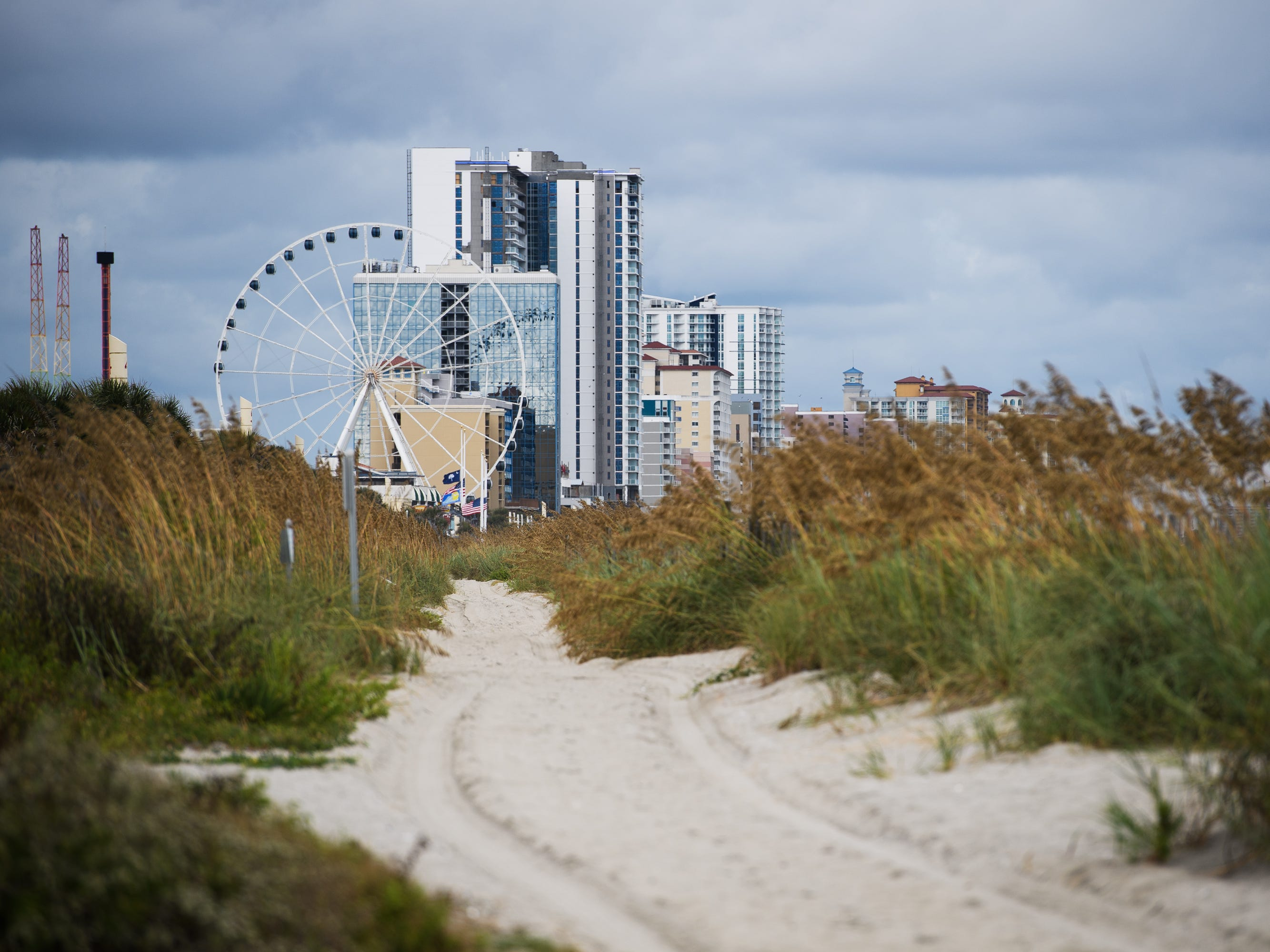 The SkyWheel and various high rises in Myrtle Beach are visible at the end of a path cut through beach grass and sand dunes along the shore on Tuesday, Sept. 11, 2018.