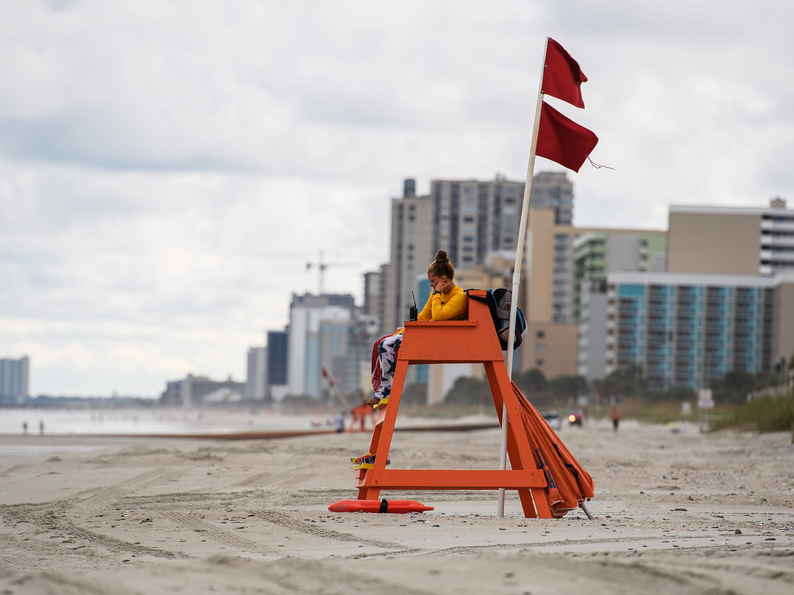 A lifeguard sits on duty at a nearly vacant beach in Myrtle Beach the day of the mandatory evacuation for Hurricane Florence on Tuesday, Sept. 11, 2018.