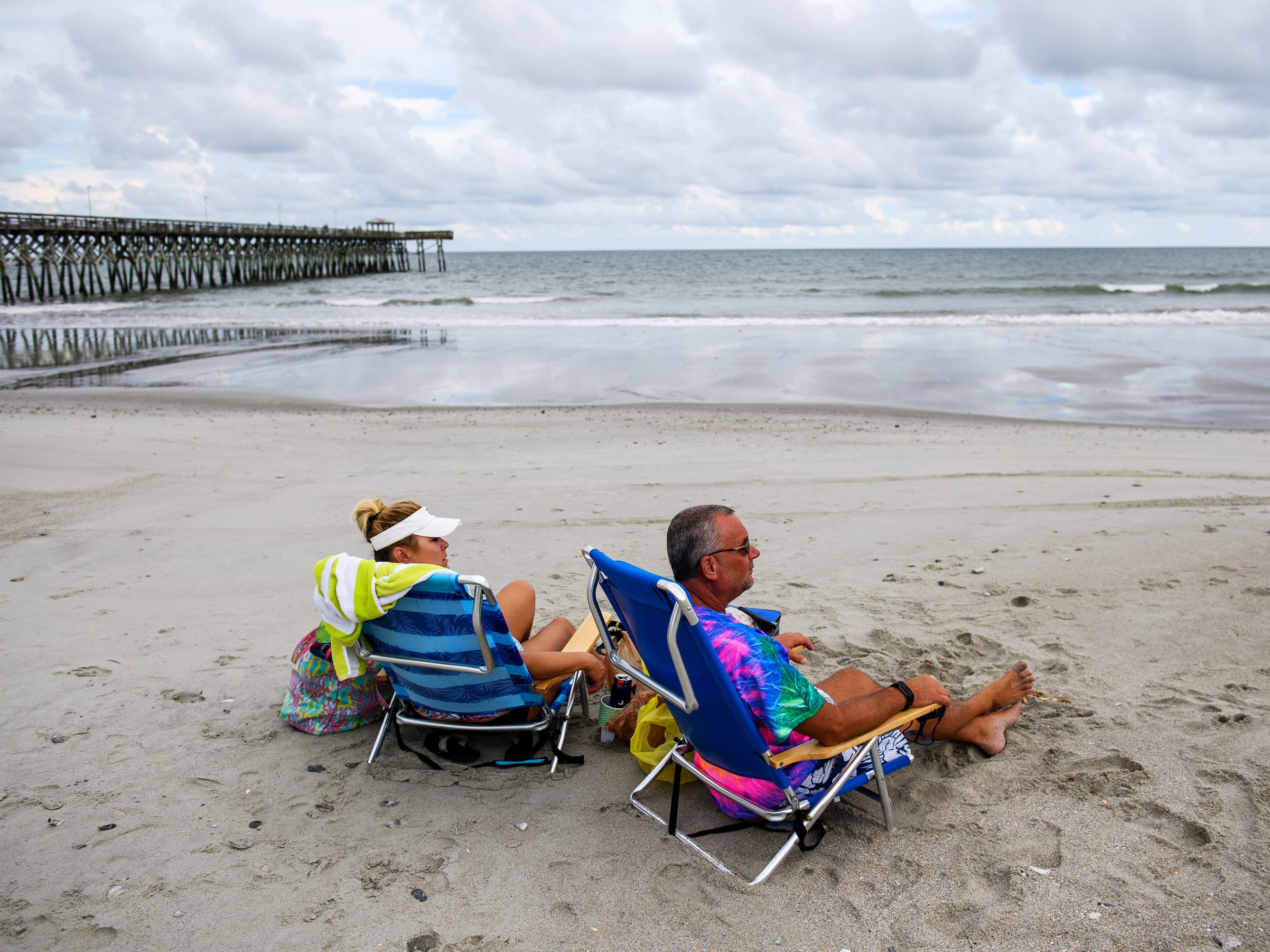 Glenn Hughey and his wife Mary enjoy a nearly vacant beach at Myrtle Beach on Tuesday, Sept. 11, 2018, days before Hurricane Florence is expected to hit coastal areas in South and North Carolina. Hughey said they live just outside of the mandatory evacuation area in Myrtle Beach and will ride out the storm.