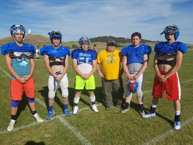 Grass Range-Winnett seniors, from left, Ryan Drollinger, Zane Stahl, Caleb Hess, Toston Browning and Caden McCarthy pose with head coach TJ Smith.