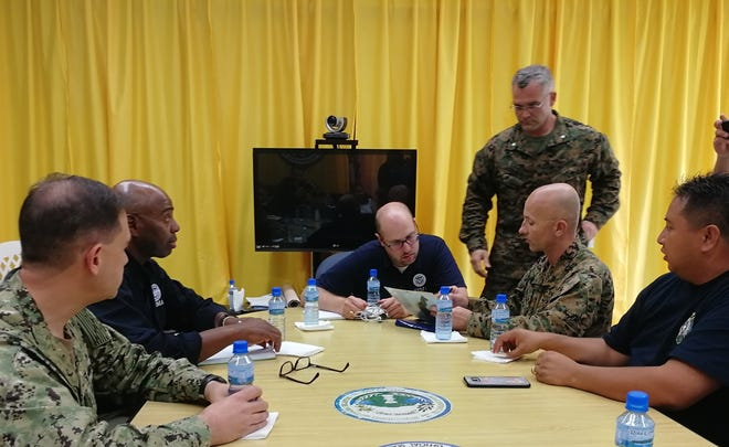 "ROTA, Commonwealth of the Northern Mariana Islands – Navy Rear Adm. Brad Cooper, left, Marine Corps Col. Robert ""Bams"" Brodie, and Lt. Col. Christopher Johnson, standing, discuss defense support of civil authorities with the Hon. Ralph Torres, governor of the Commonwealth of Northern Mariana Islands Islands and representatives from the Federal Emergency Management Agency during a meeting at the local government office, Sept. 11, 2018. Service members from Indo-Pacific Command are providing Department of Defense support to FEMA, and working with Guam and the CNMI's civil and local officials for Typhoon Mangkhut recovery efforts. Cooper is the Combined Task Force 76 commander, Brodie is the 31st Marine Expeditionary Unit commanding officer, and Johnson is the Combat Logistics Battalion 31 commanding officer."