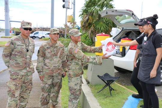 Guam Guard Soldiers are all smiles as they receive donations of burgers from Wendy's employees, on Sept. 12, in appreciation for the hard work.