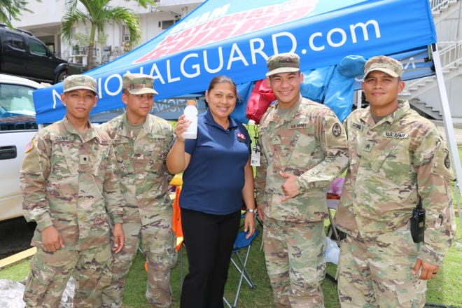 Guam Guard Soldiers pose for a photo with a 76-Circle K employee, on Sept. 12, after she donated drinks in appreciation for the hard work they were doing for the community as they conducted traffic control on Route 4 in Sinajana.