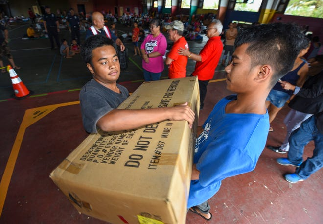 Shelterees help unload a truckload of boxes containing folding sleeping cots at the Astumbo Gym, Tier II shelter in Dededo on Wednesday, Sept. 12, 2018. A total of 280 cots, provided by the American Red Cross Guam Chapter, were delivered to the shelter for registered occupants to use during their stay, said Dave Peredo, American Red Cross Guam Chapter disaster program manager.